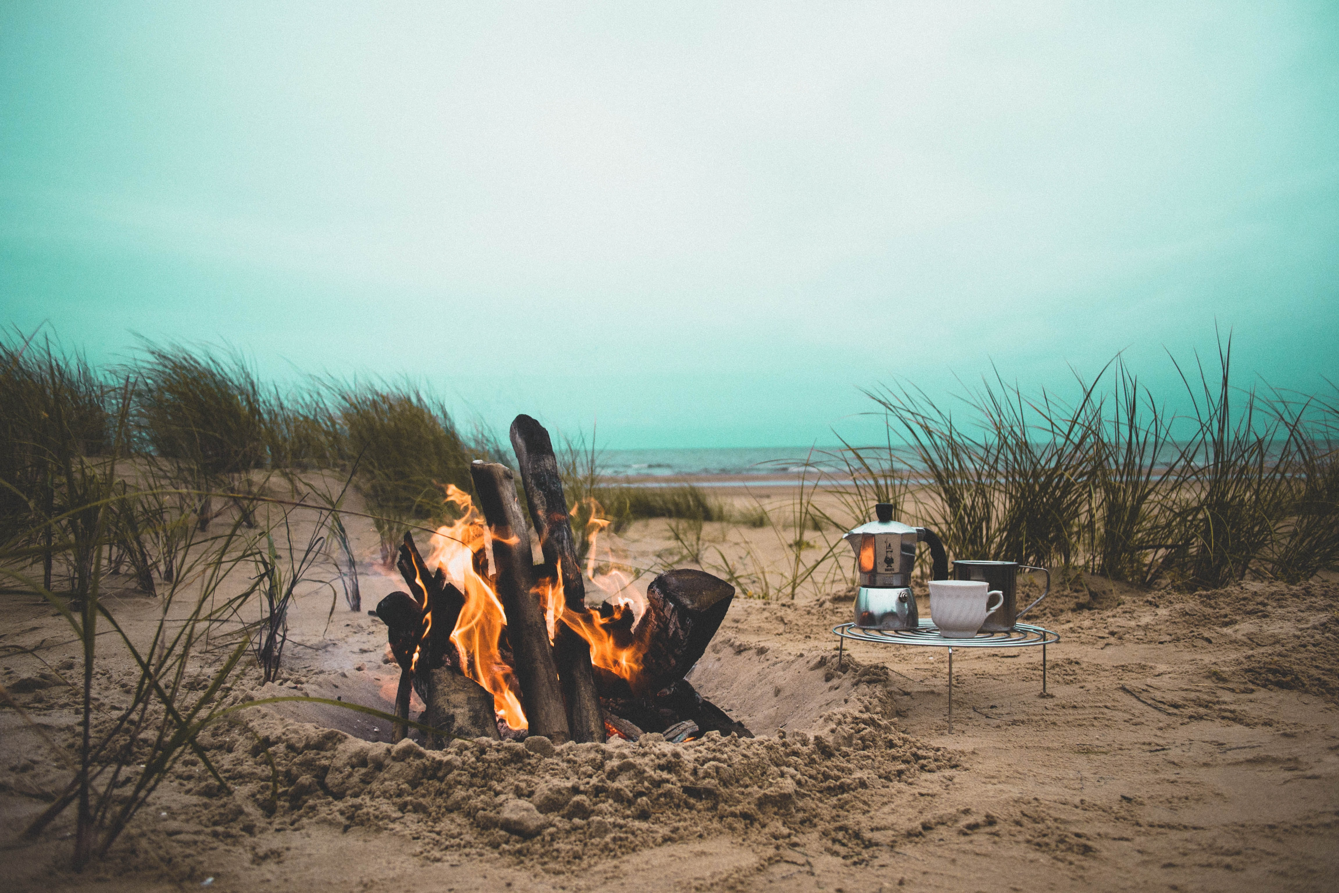 Kettle and a cup on a stand by the large fire in the sand hole