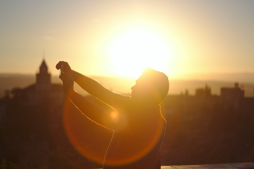 man raising hands under sunset
