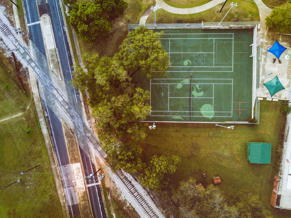 high angle photo of green lawn tennis court near trees, road, and railway