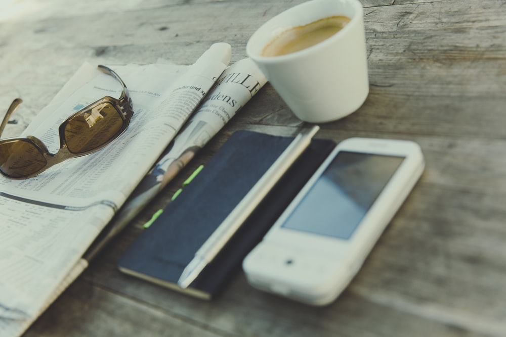 white digital device beside click pen