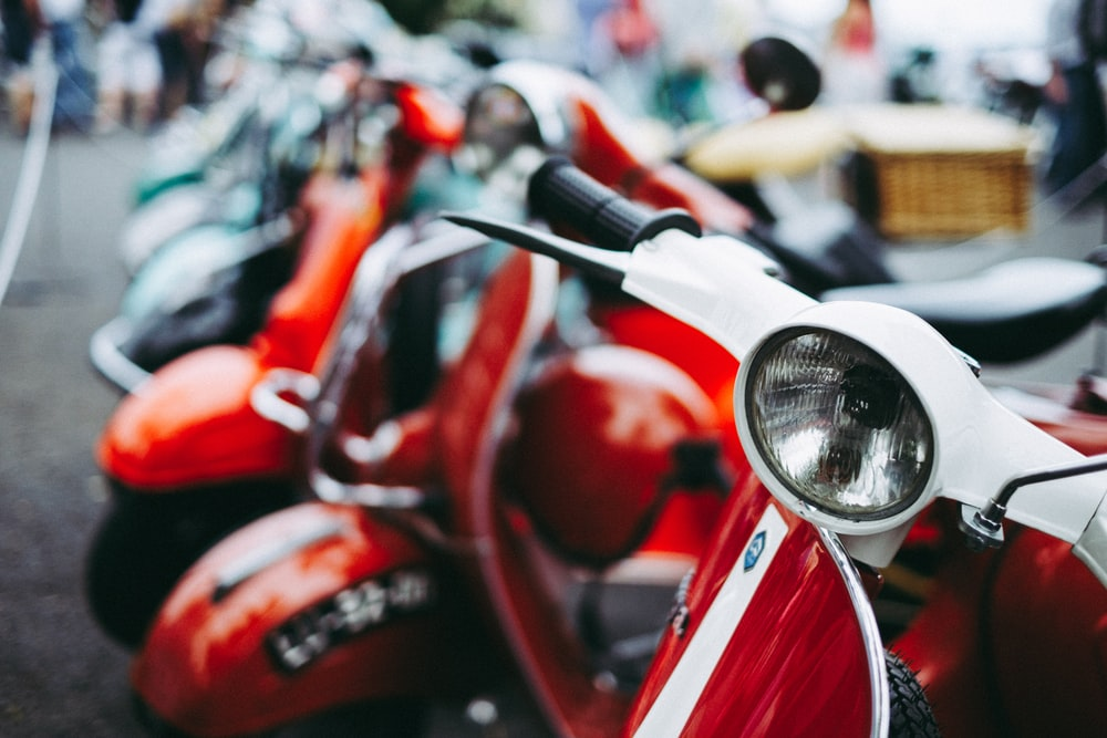 red and white motor scooter parked selective photography