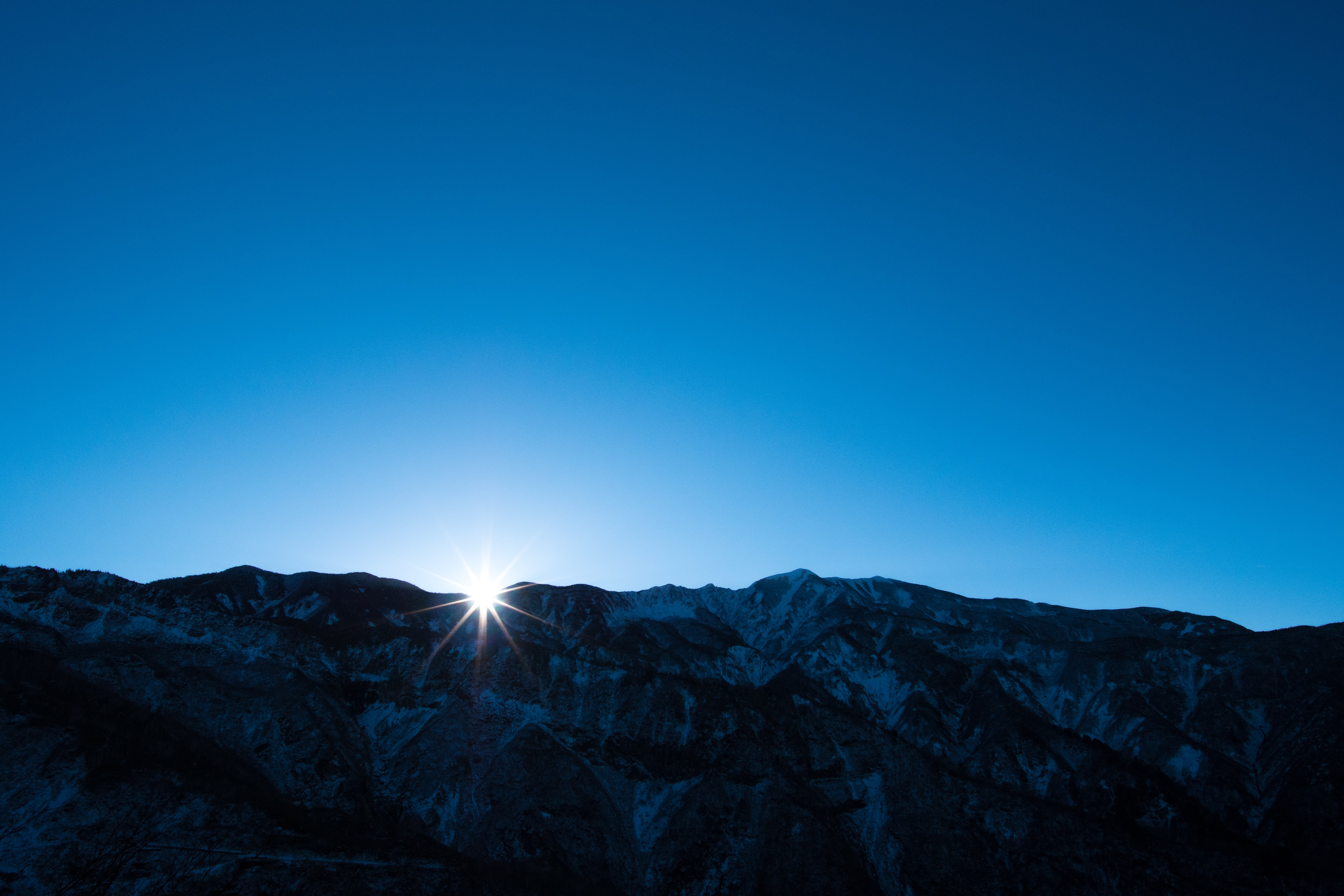 Bright sun emerging from behind a snowy mountain ridge during sunrise
