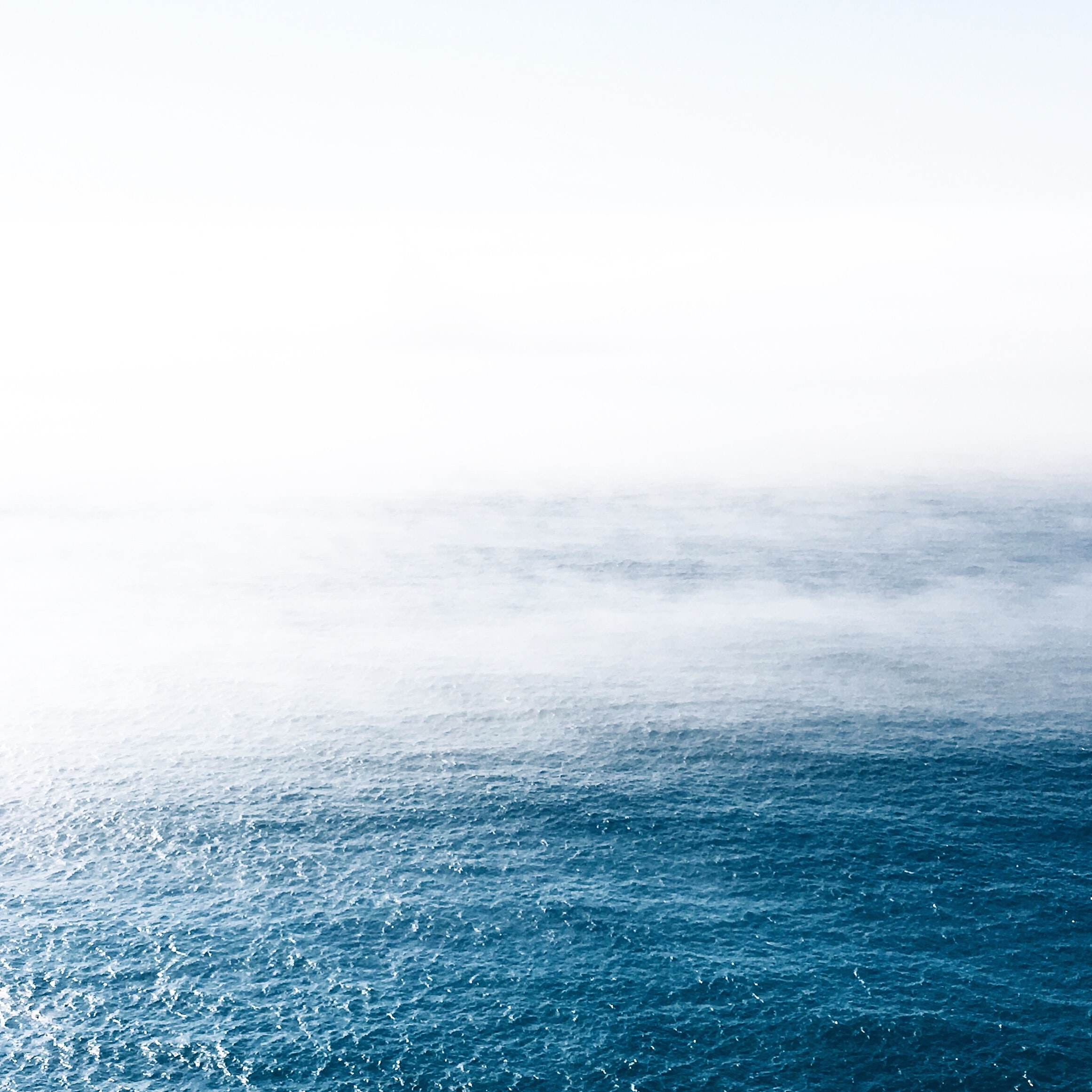 Fog rolls over wavy blue waters in Portugal