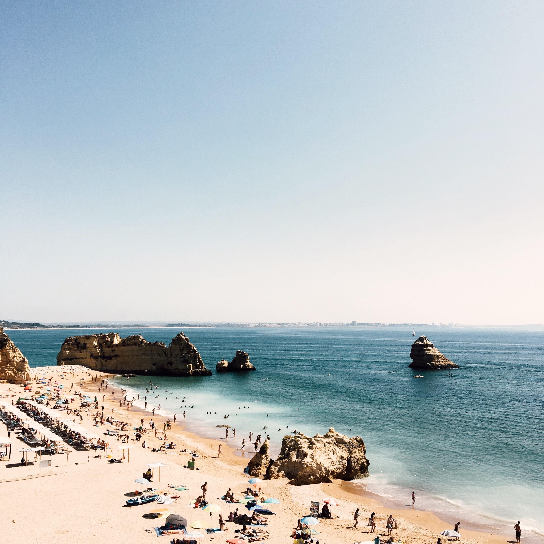 Crowded sand beach with rocks on a sunny day in Lagos, Distrito de Faro, Portugal