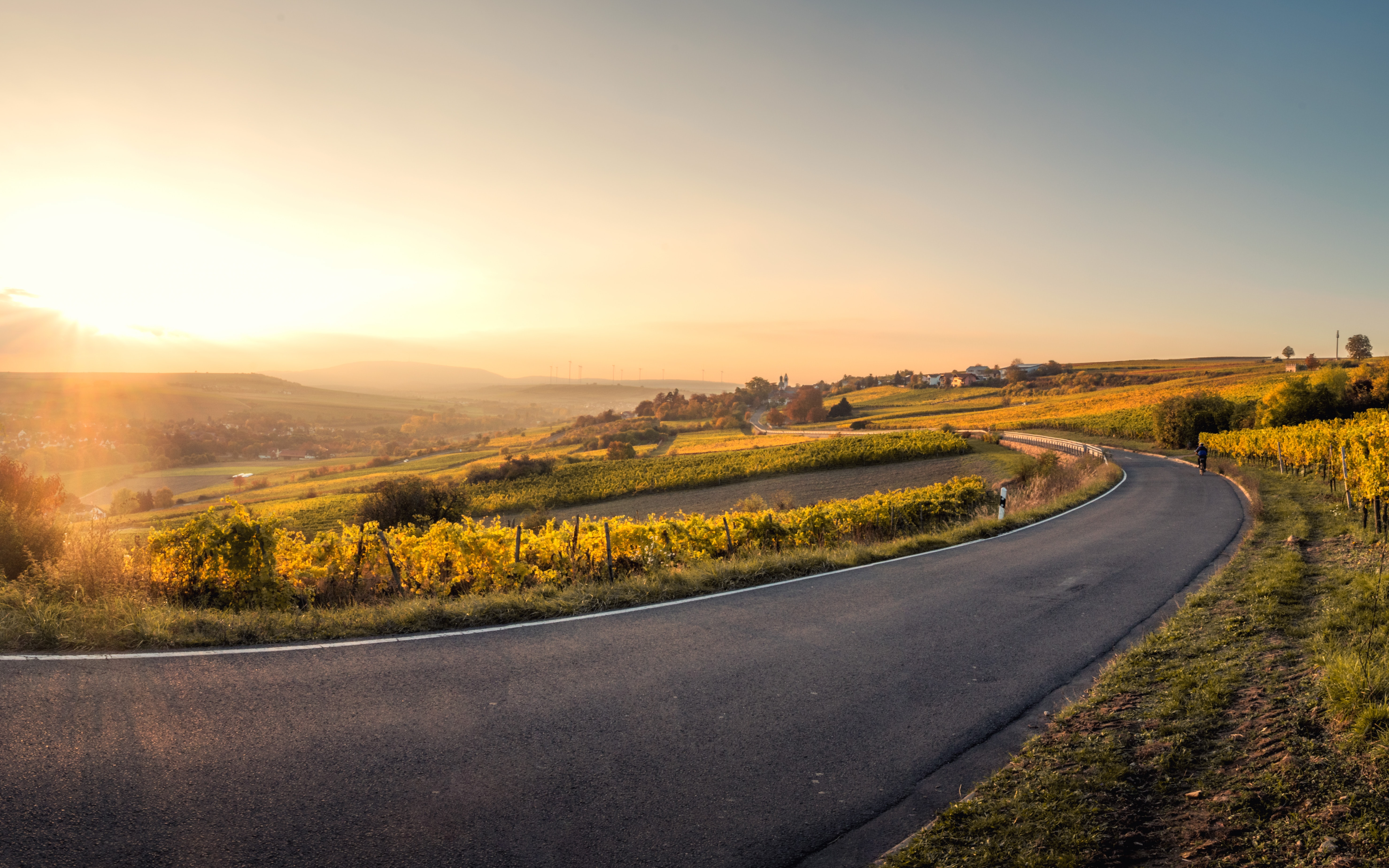 A sunset shines upon a winding asphalt road in Mölsheim, Germany and the many fields surrounding it