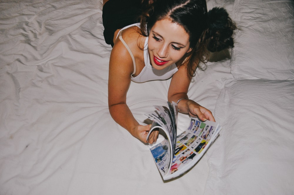 smiling woman lying on bed while reading magazine