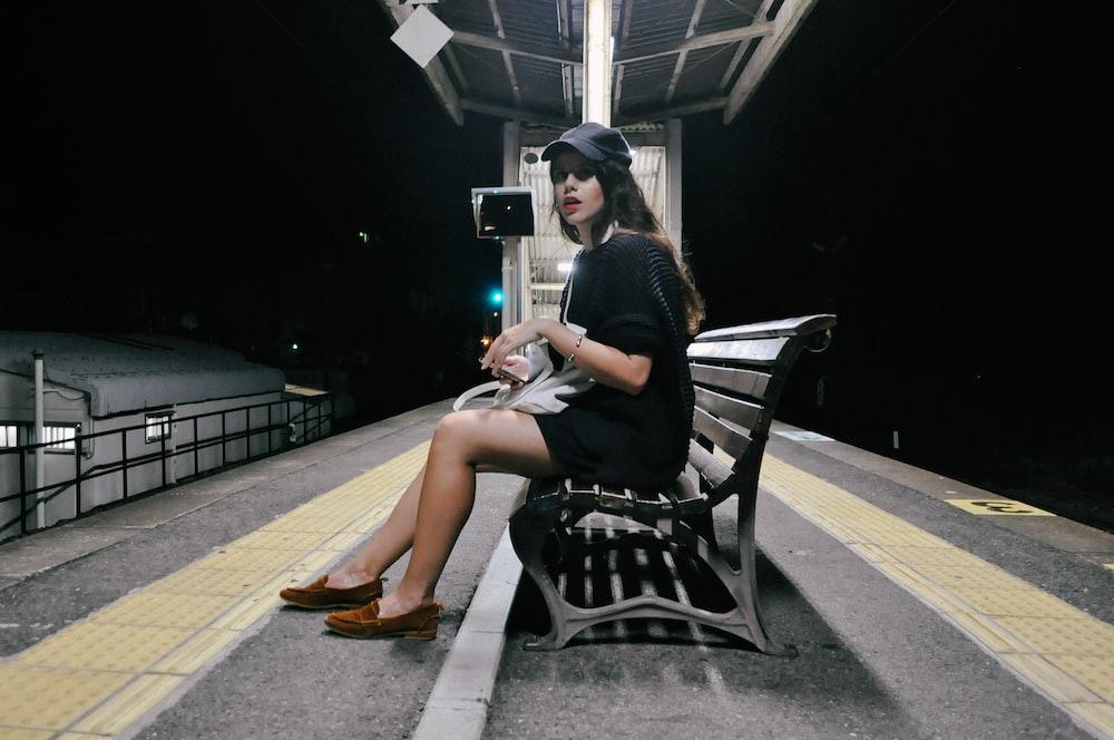 woman wearing black dress sitting on the
