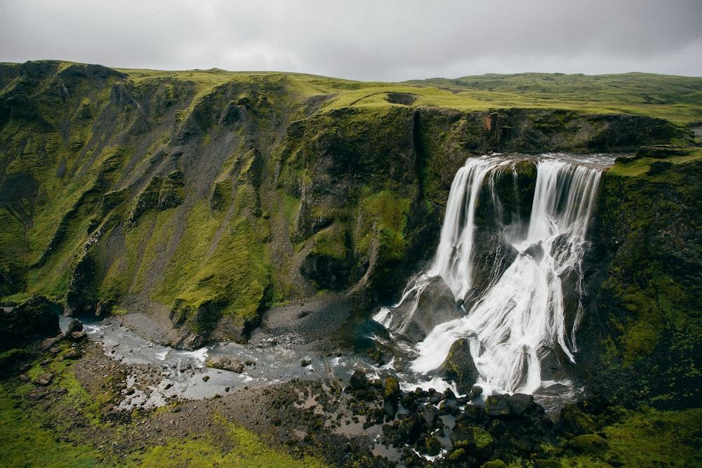 waterfalls beside green mountain