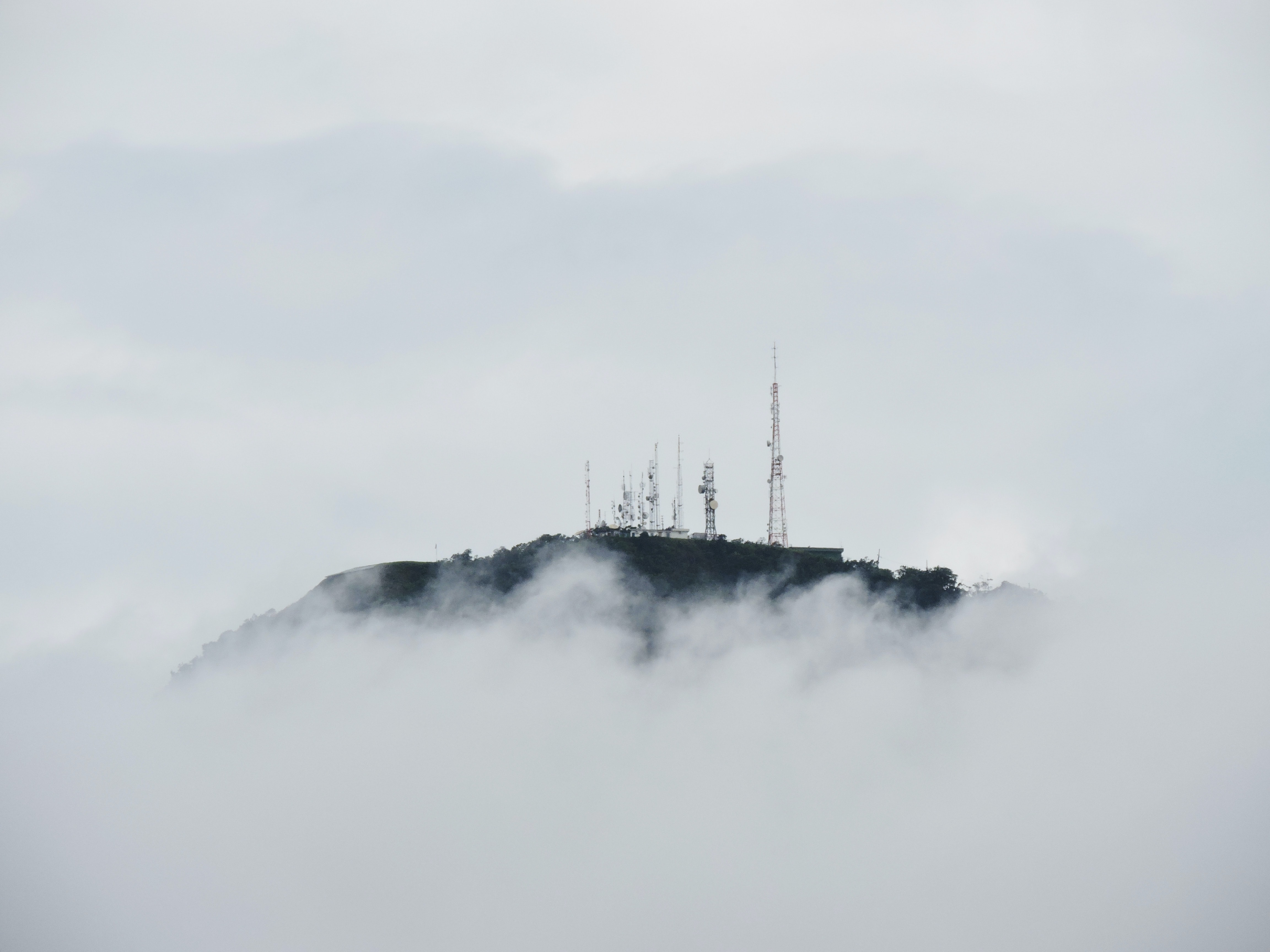 Radio towers on top of a cloud-shrouded mountain in Brazil