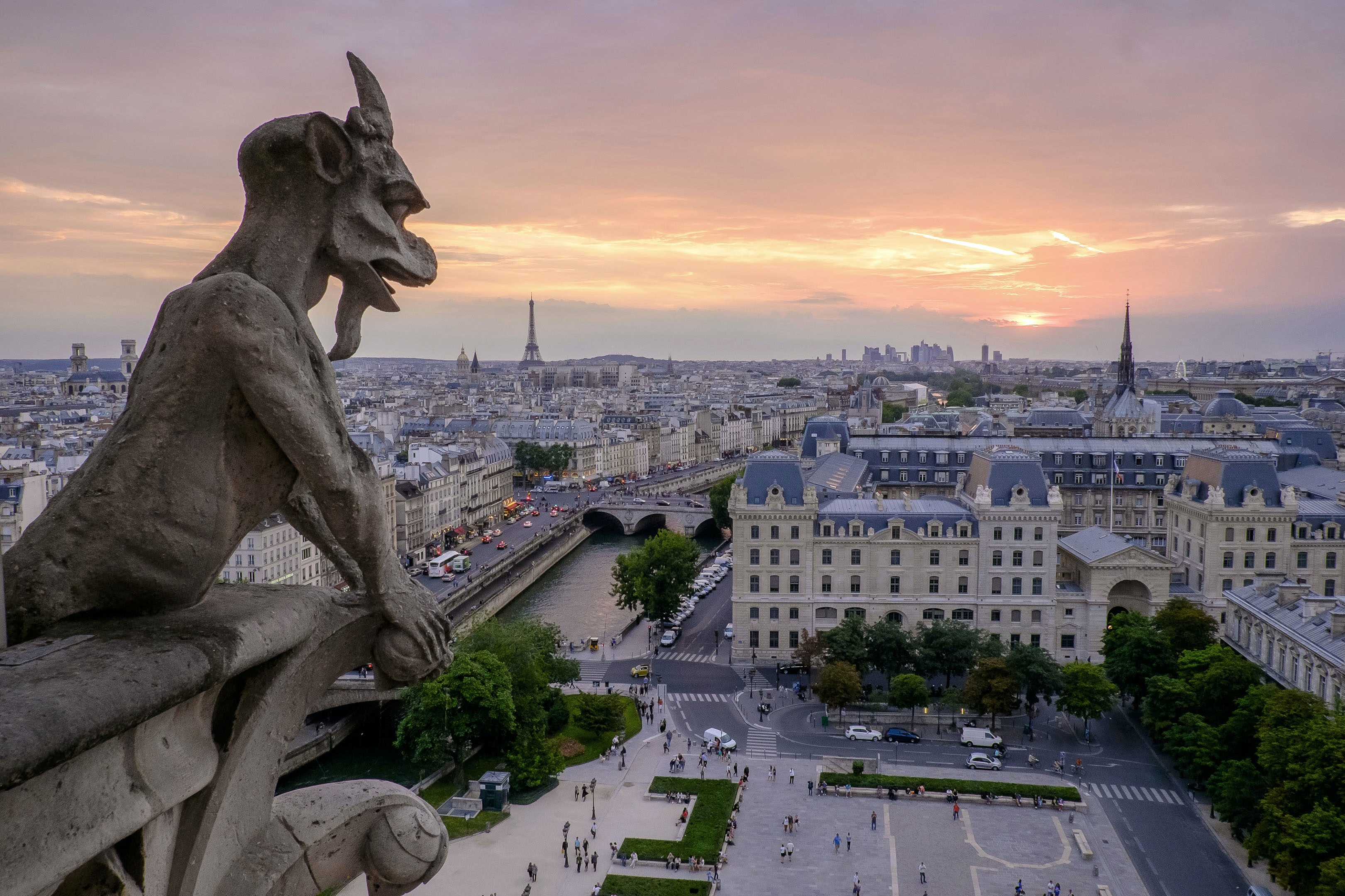 A gargoyle looks over the Notre-Dame Cathedral in Paris with a pale sunset lighting up the cityscape horizon.