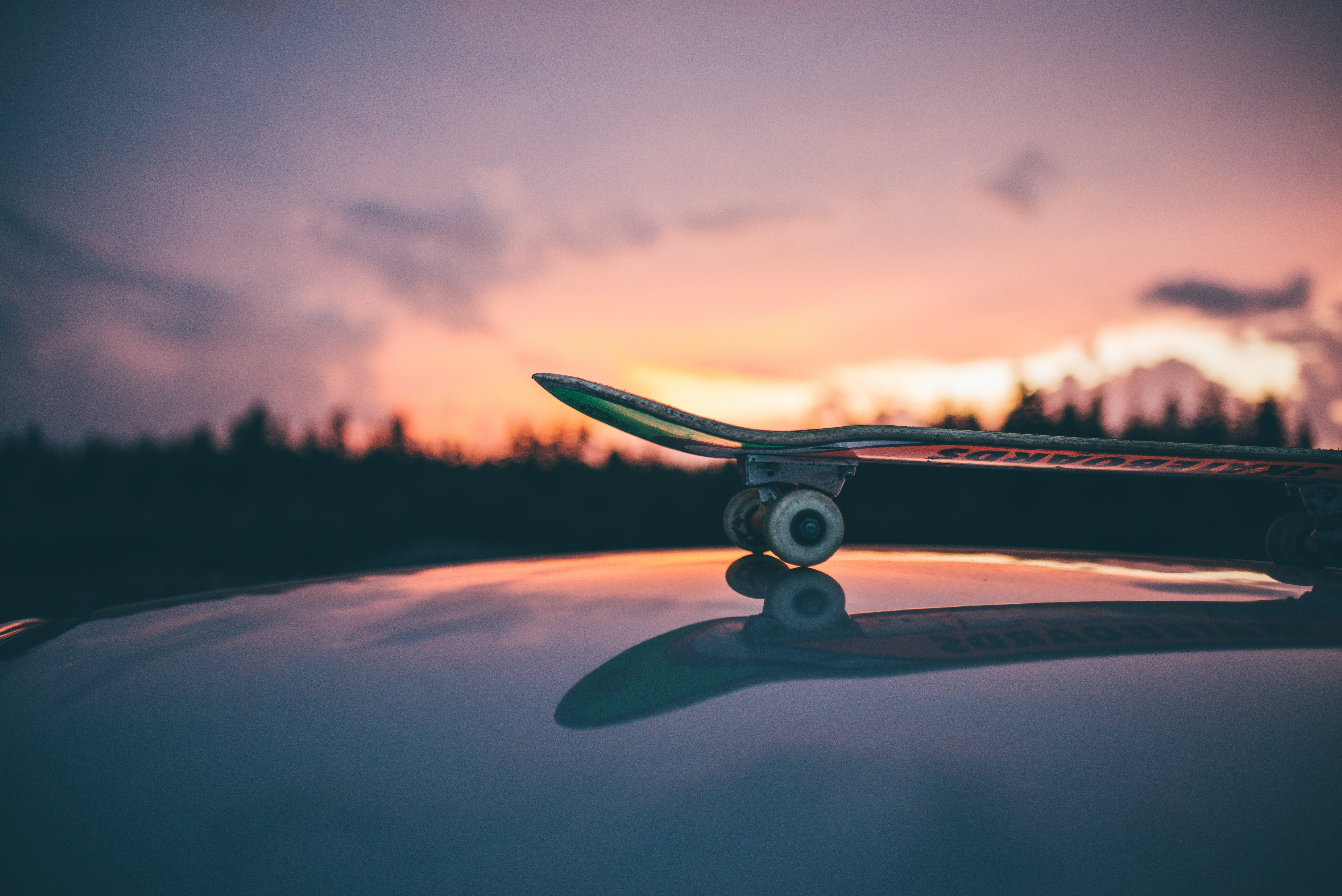A skateboard on a reflective surface, with trees in the background and a purple sunset sky, Norrköping