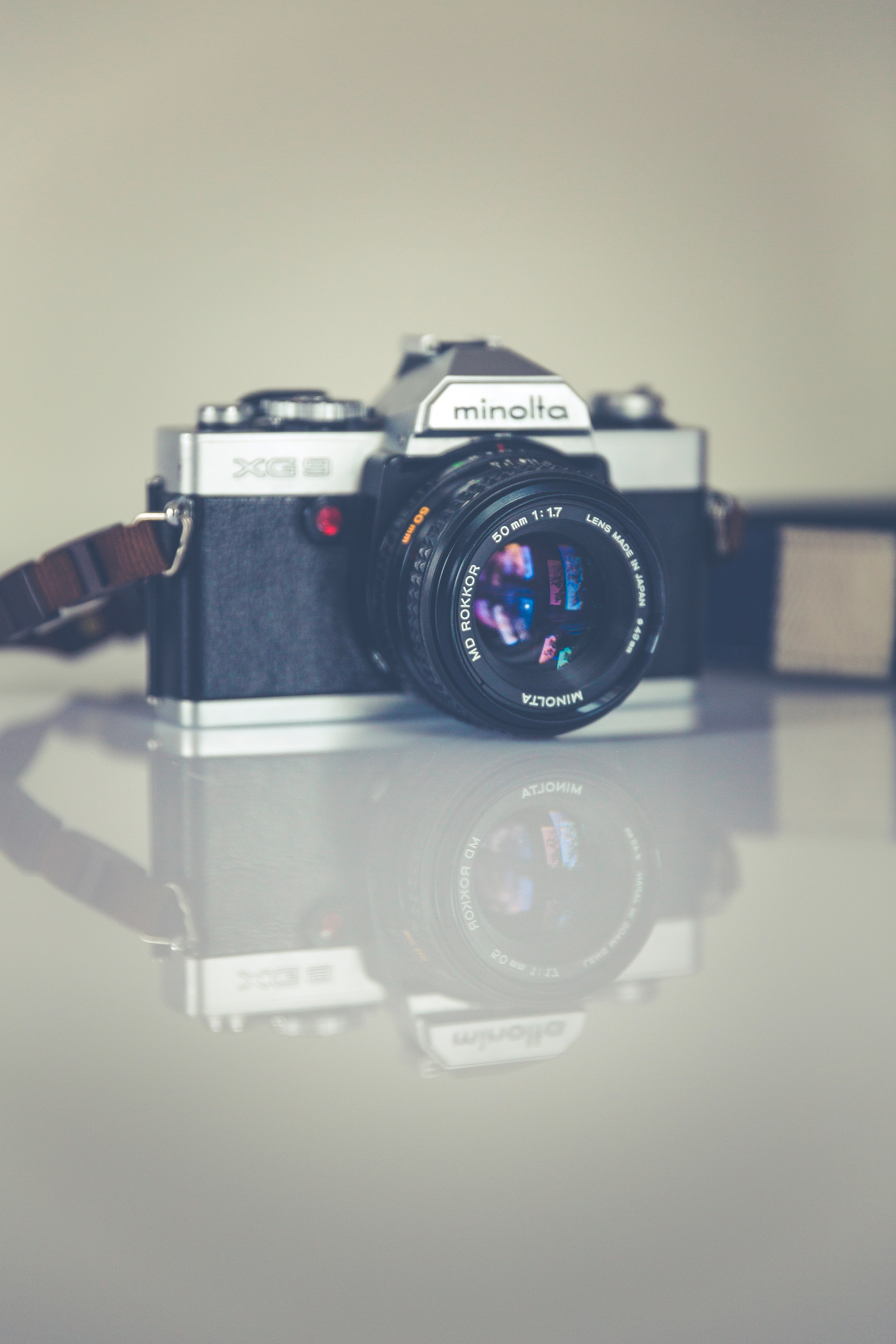 Photographer's vintage film camera on a reflective table