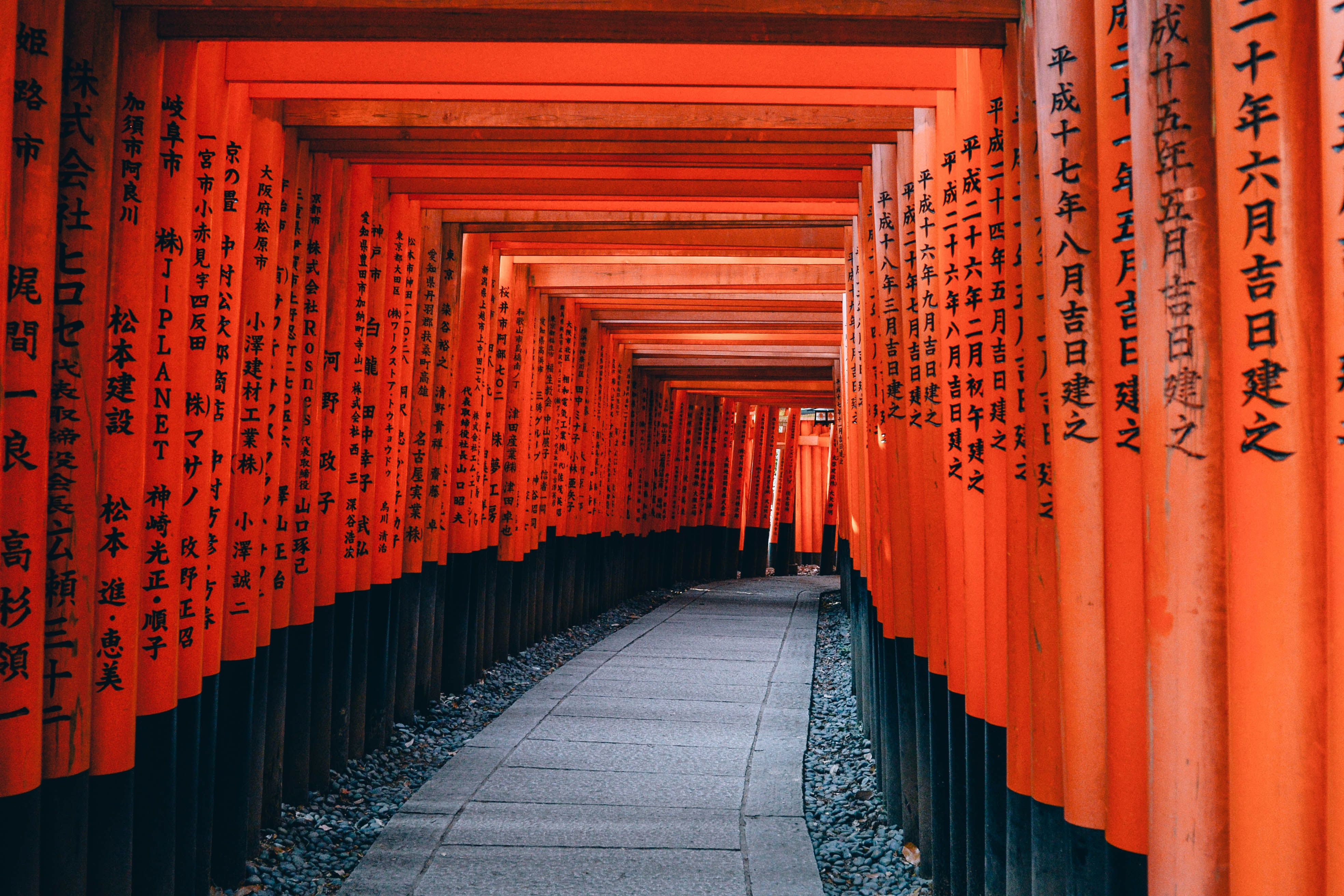 An orange walkway path with consistent architecture at Fushimi inari Trail leading to the shrine