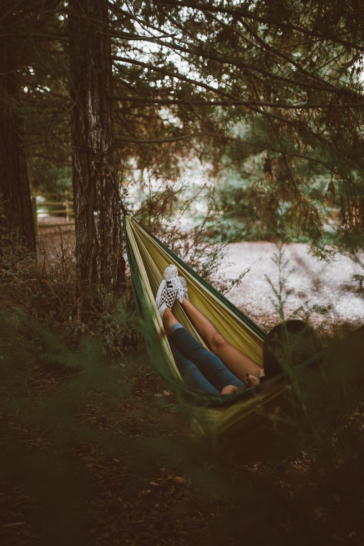 person on yellow hammock hanging on tree