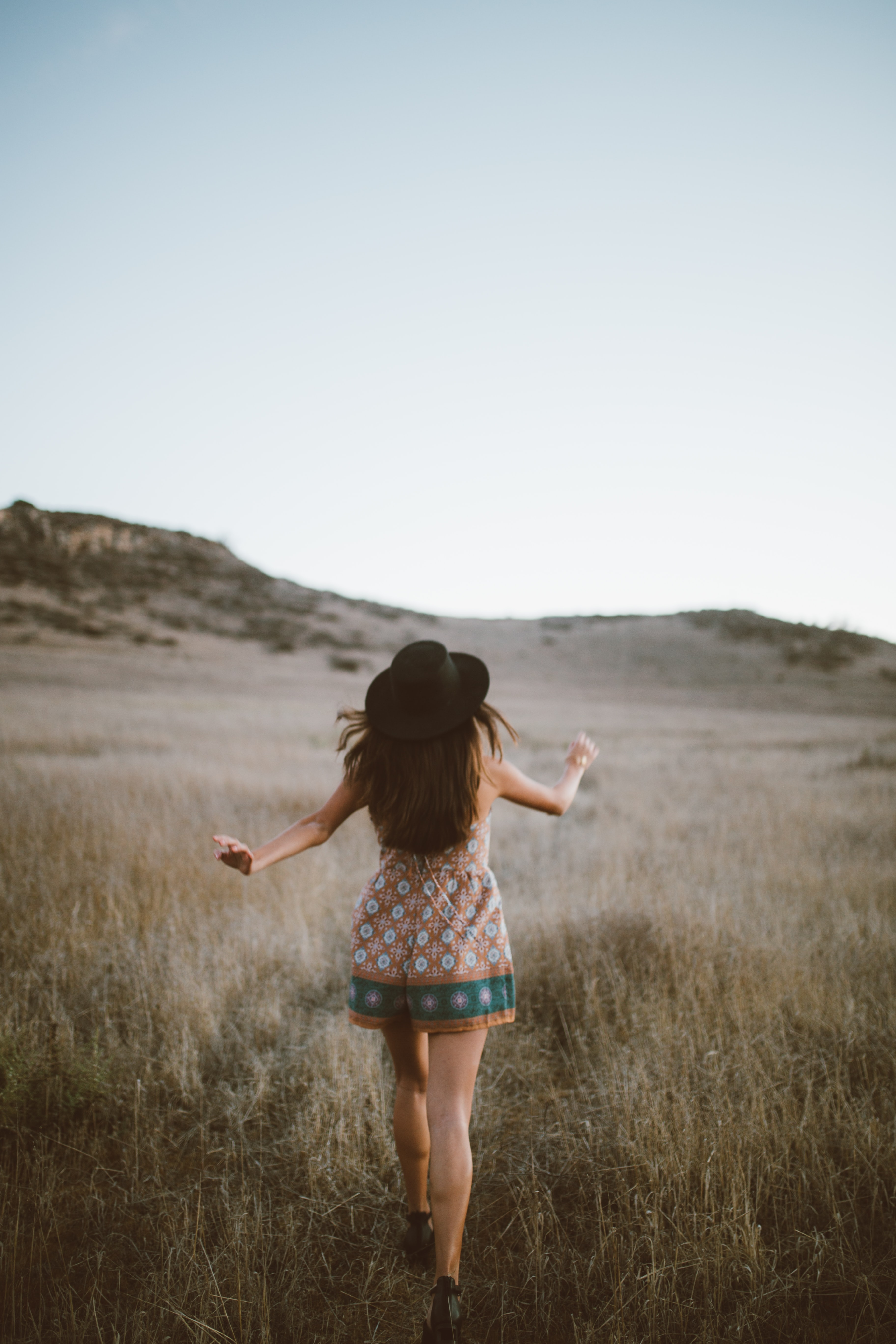 woman wearing brown and green floral romper walking on green grass