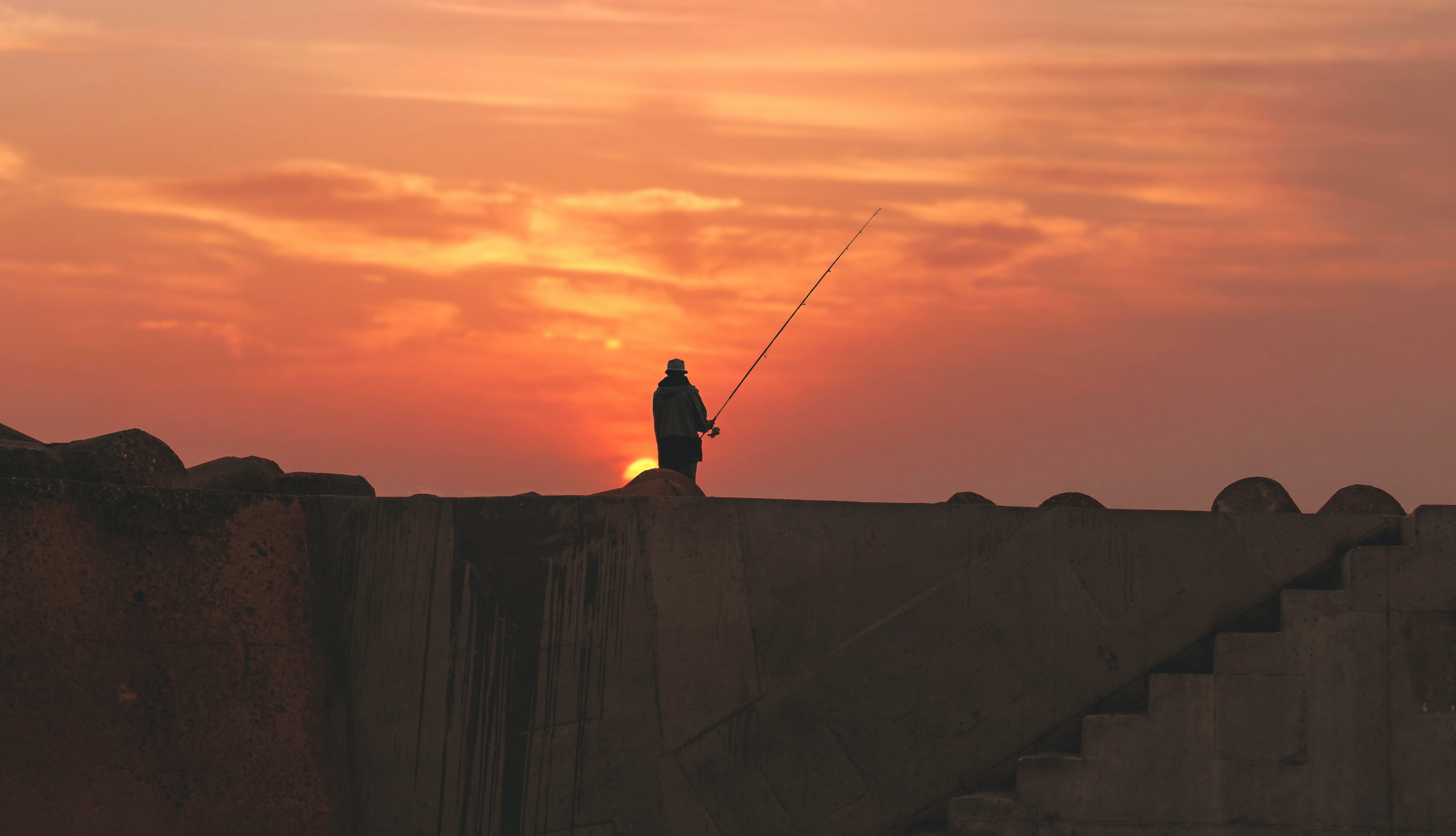 A silhouette of a fisherman standing atop a wall in Asilah, Morocco during sunset