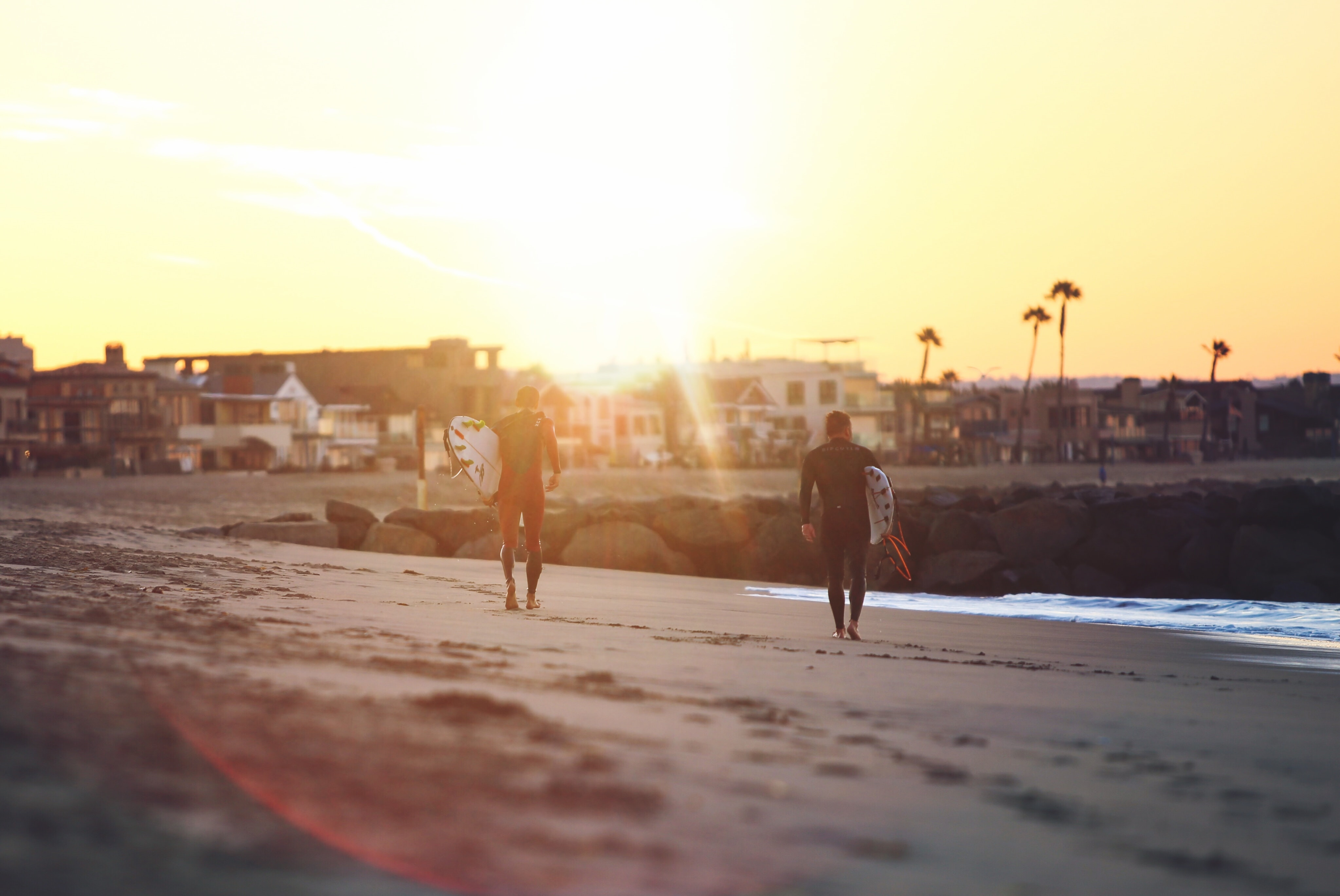 two person walking on seashore while holding surfboards
