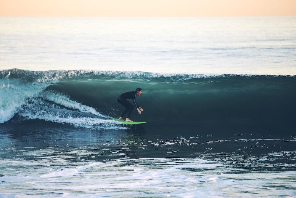 man surfing on sea at daytime