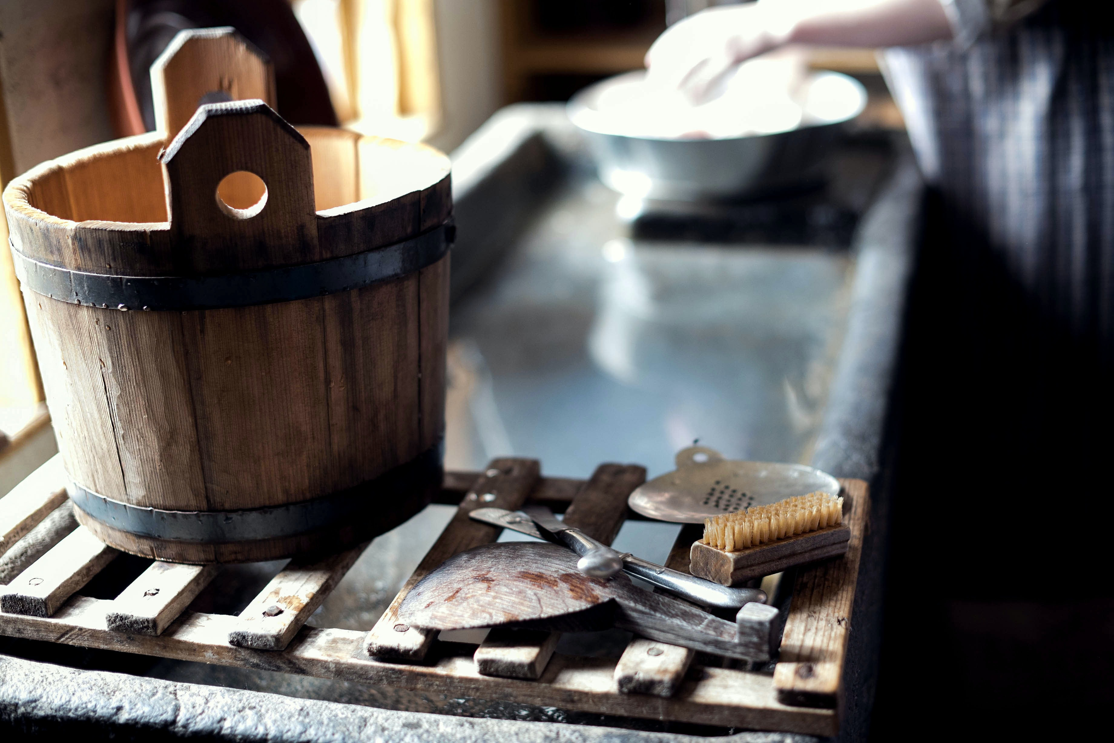 A wooden bucket, brush, and other cleaning supplies resting on a sink ledge while a person washes dishes in Sturbridge