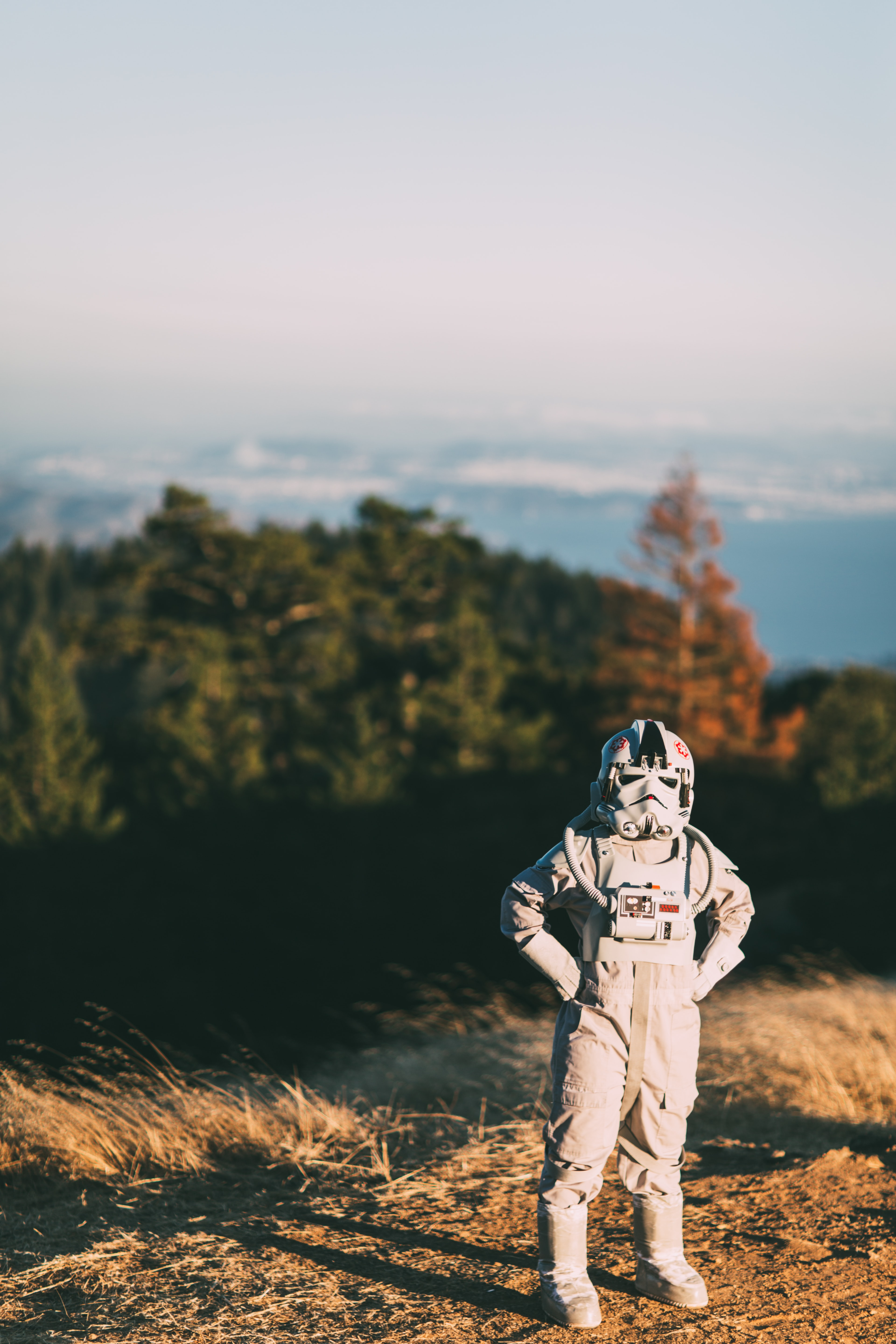 A child in a Star Wars' stormtrooper costume on a slope near a forest