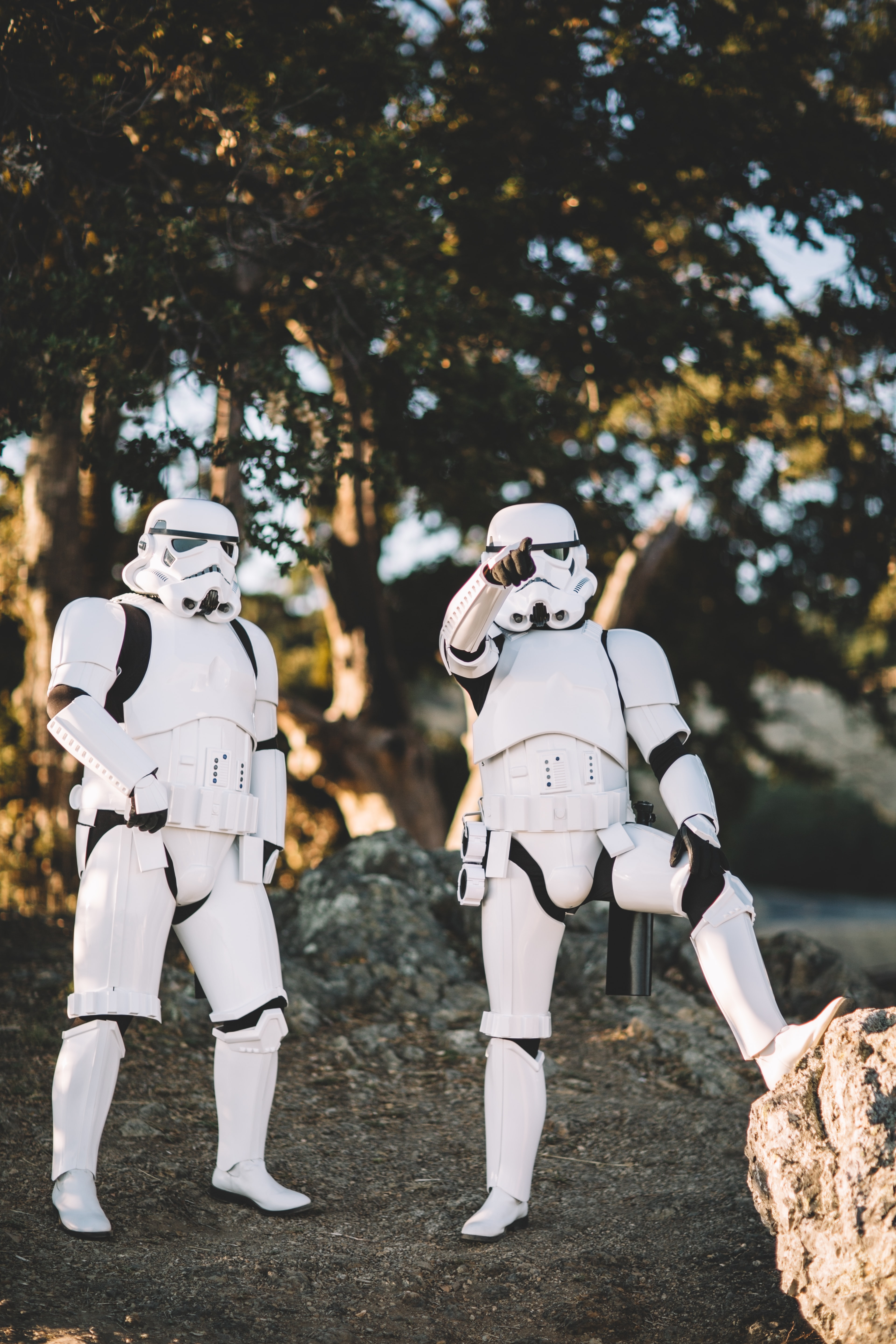 two Star Wars Stormtrooper action figures on gray surface outdoors