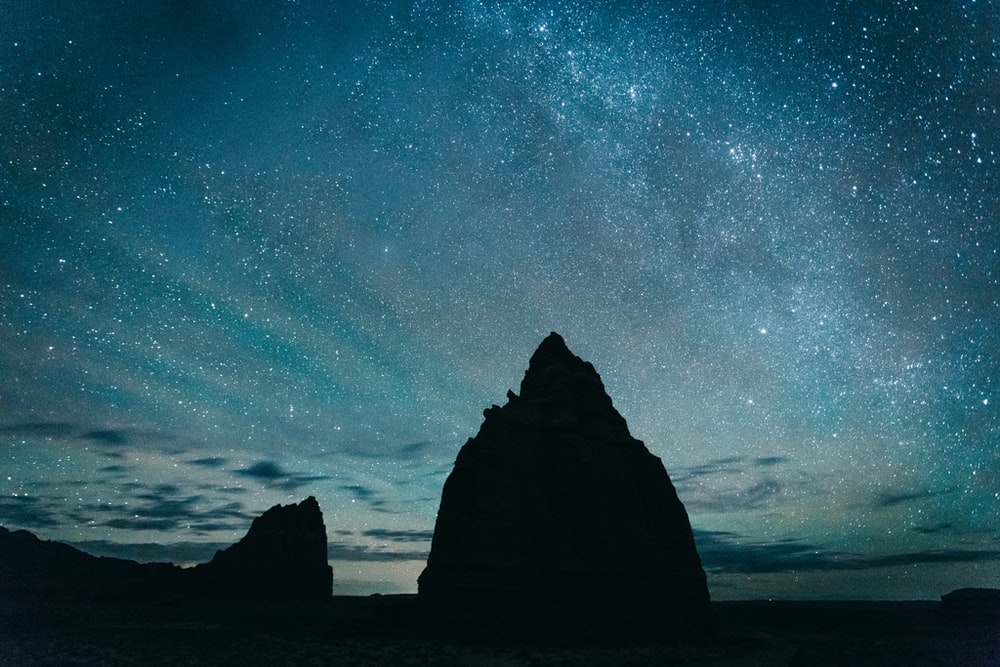silhouette of rocky mountain under starry sky