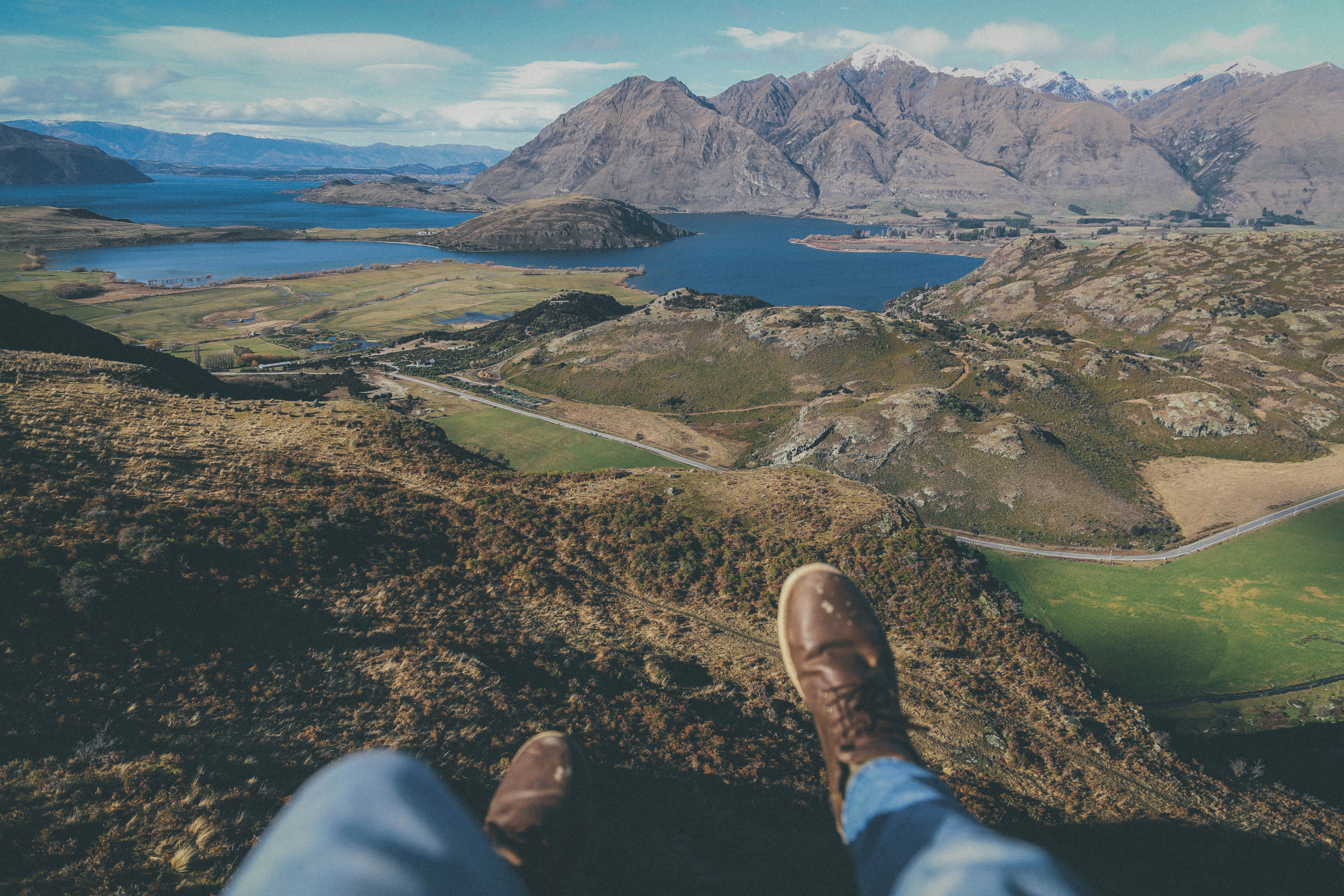 A person's legs dangling off from a hill over mountain lakes in New Zealand