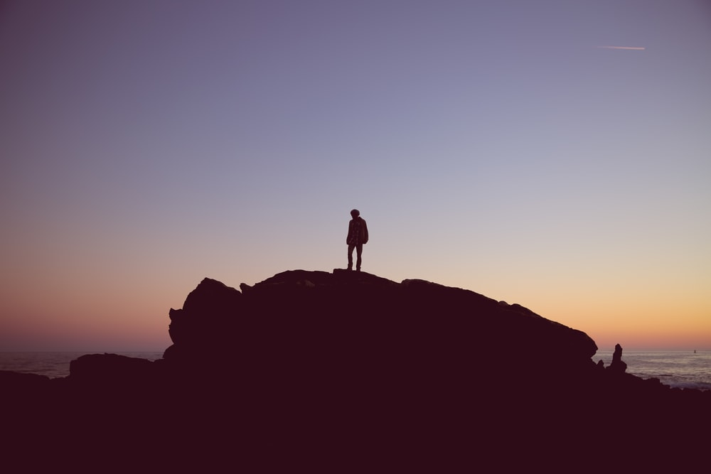 A silhouette of a person on a large rock by the sea at sunset