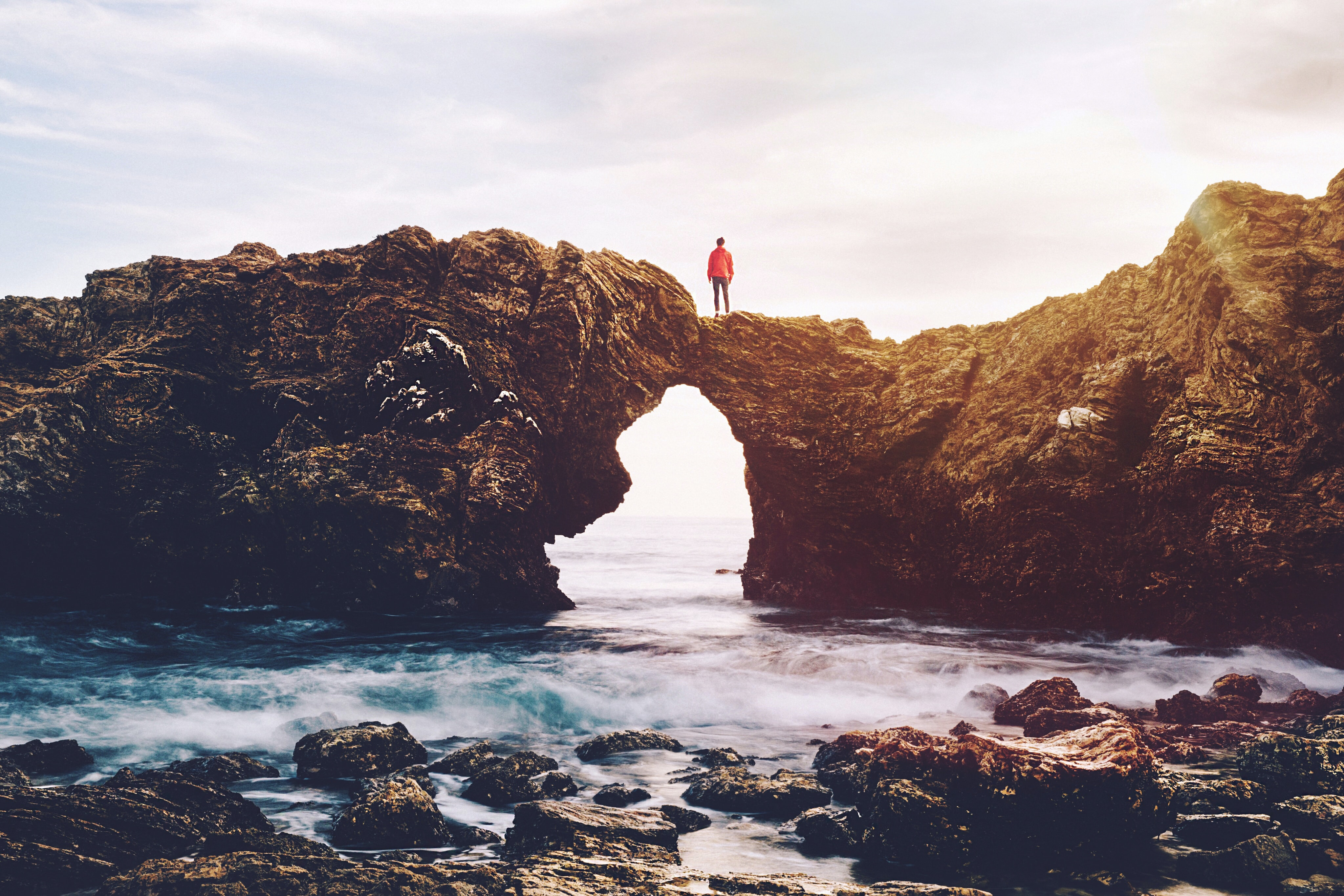 A breathtaking shot of a person standing on an arch created by a jagged cliff over water