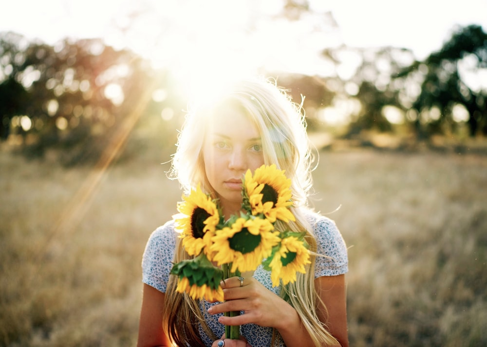 portrait photography of woman holding bouquet of sunflowers