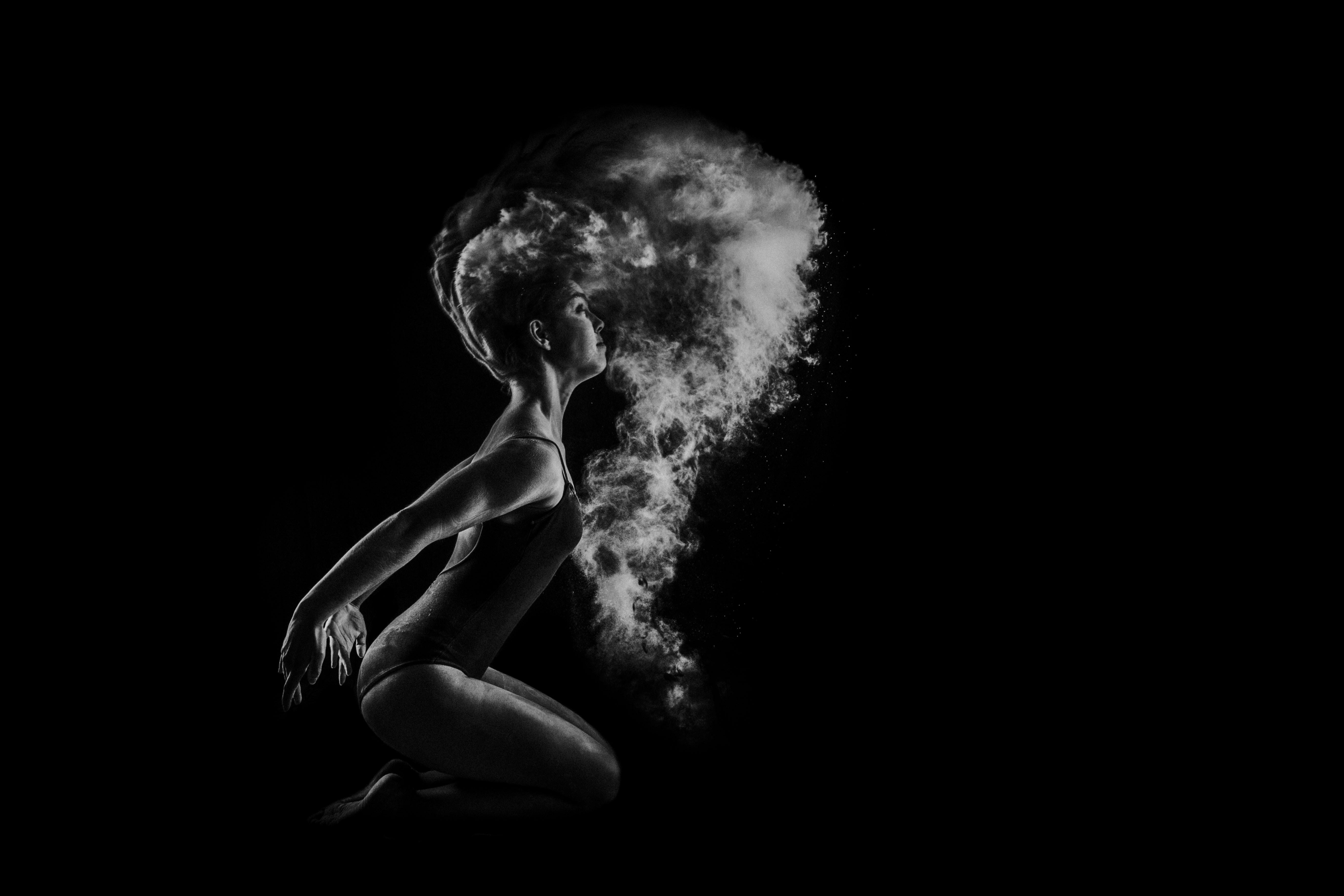 Black and white shot of female dancer kneeling with powder flying in air, Matosinhos
