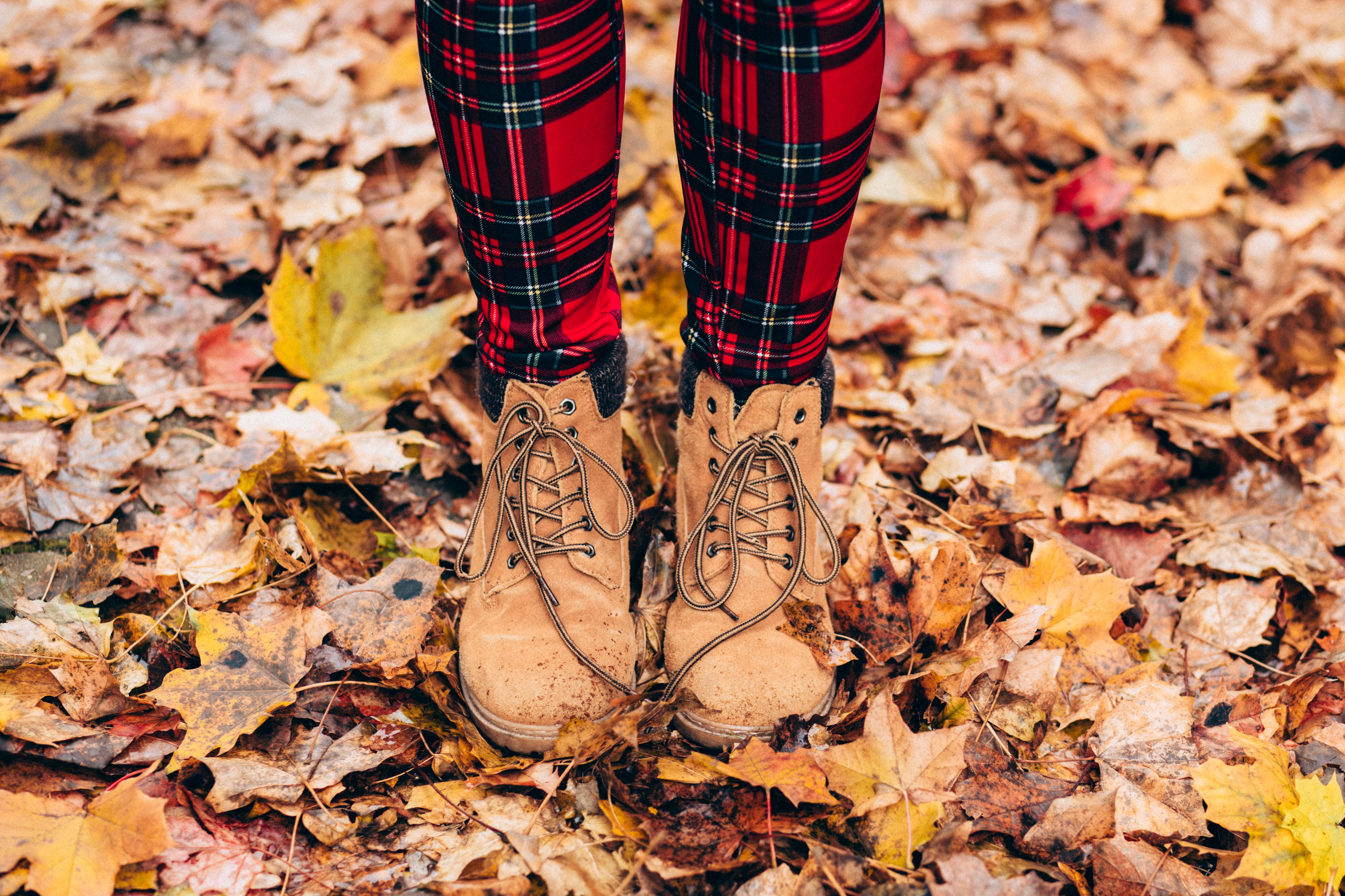 A person wearing plaid pants and boots stands on fall leaves