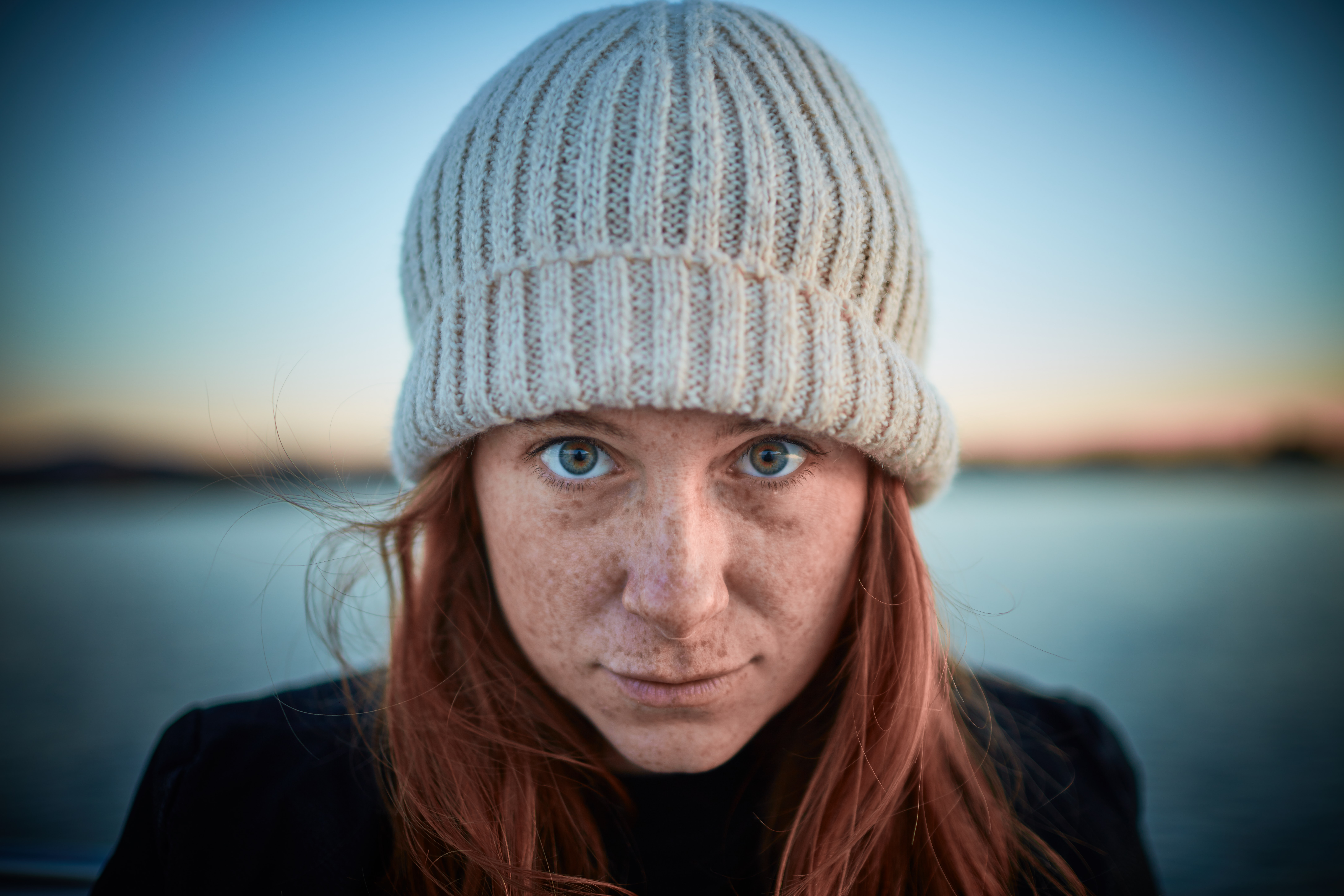 A redheaded woman with freckles and beautiful eyes wearing a grey knit hat at Smith Mountain Lake