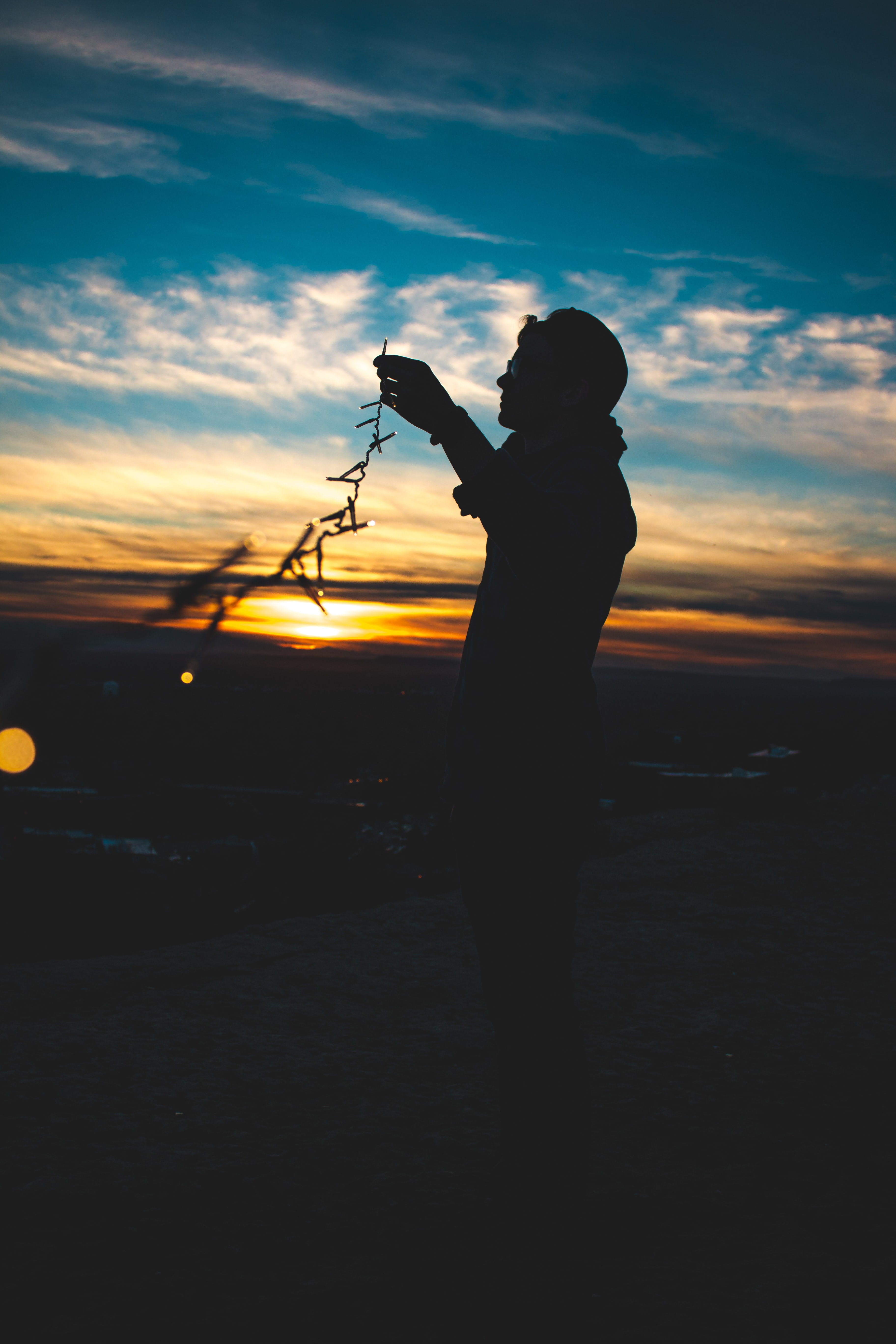 Silhouette of man with sunglasses holding fairy lights at sunrise