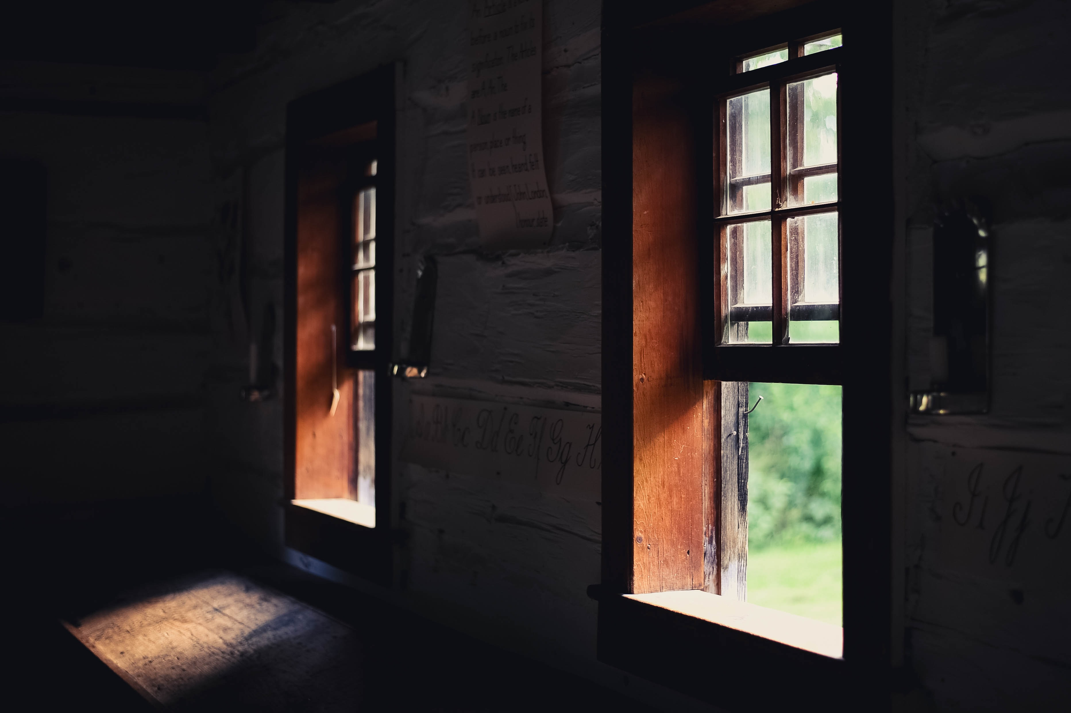 A dim shot inside an old building with sunlight coming in through open wooden windows