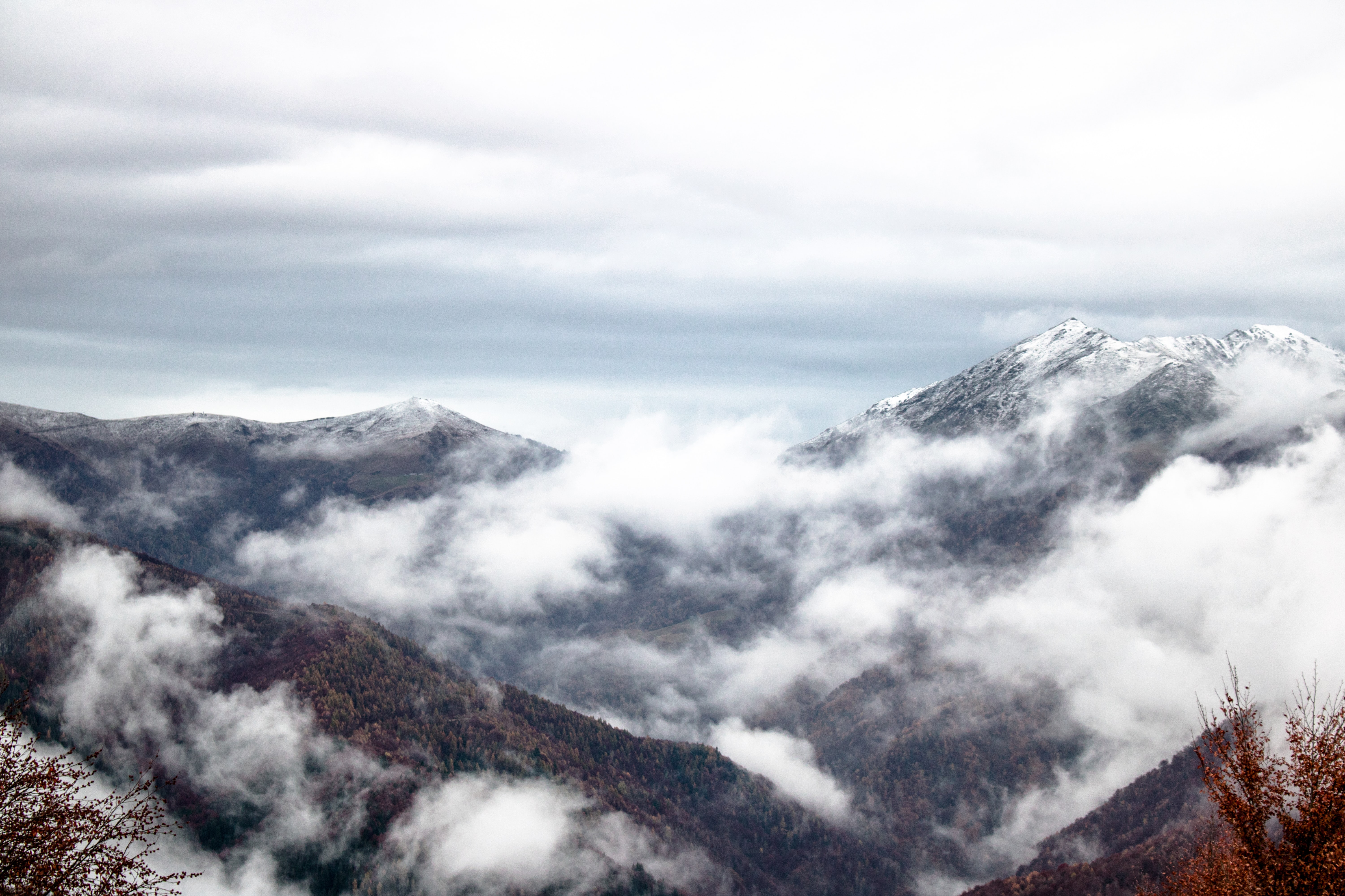 Clouds billow on mountain peaks covered in snow
