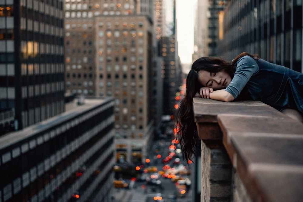 Woman with long-hair sleeping on the brick balcony edge among skyscrapers in New York