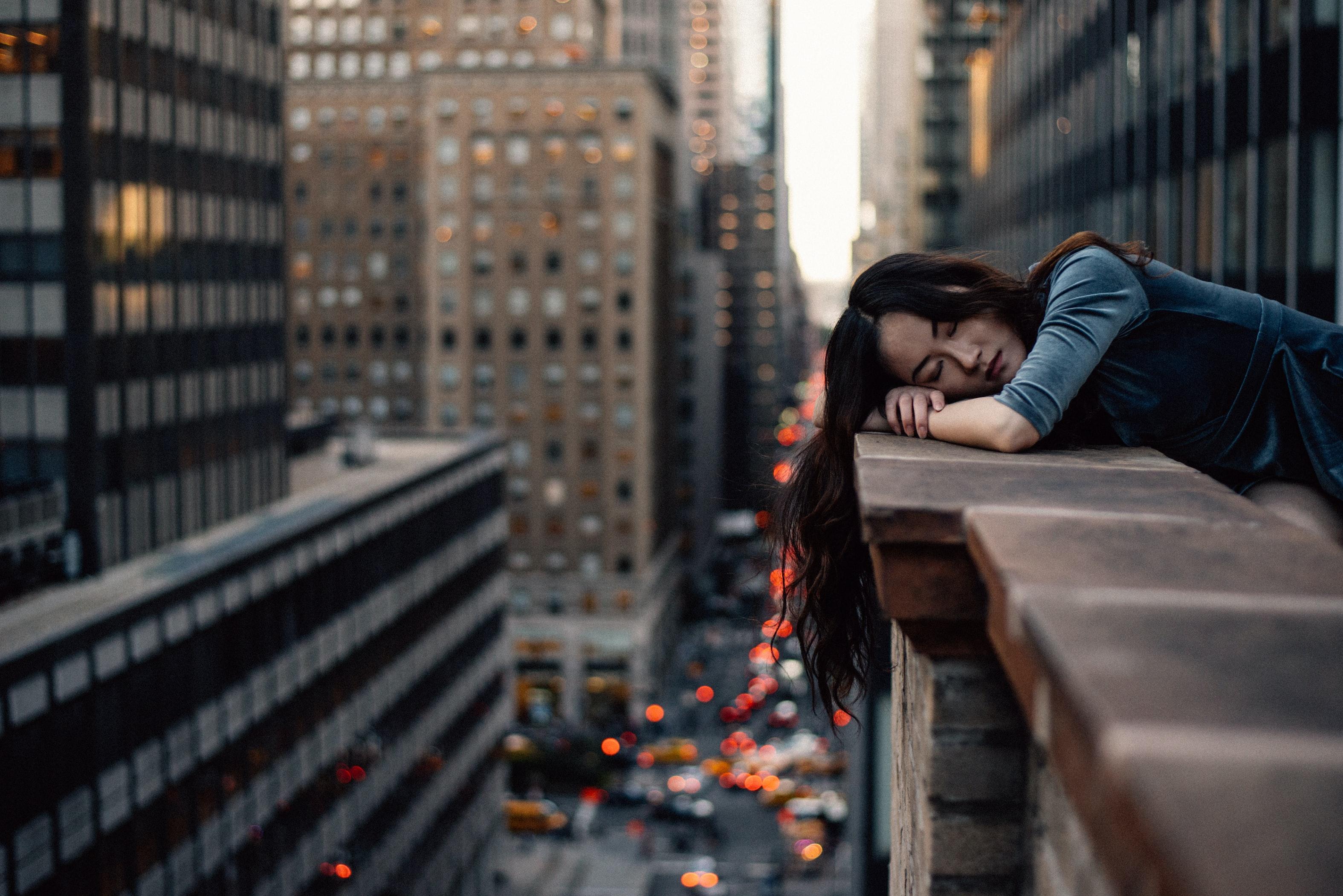 Jeune femme endormir sur le rebord de la terrasse d'un toit d'immeuble