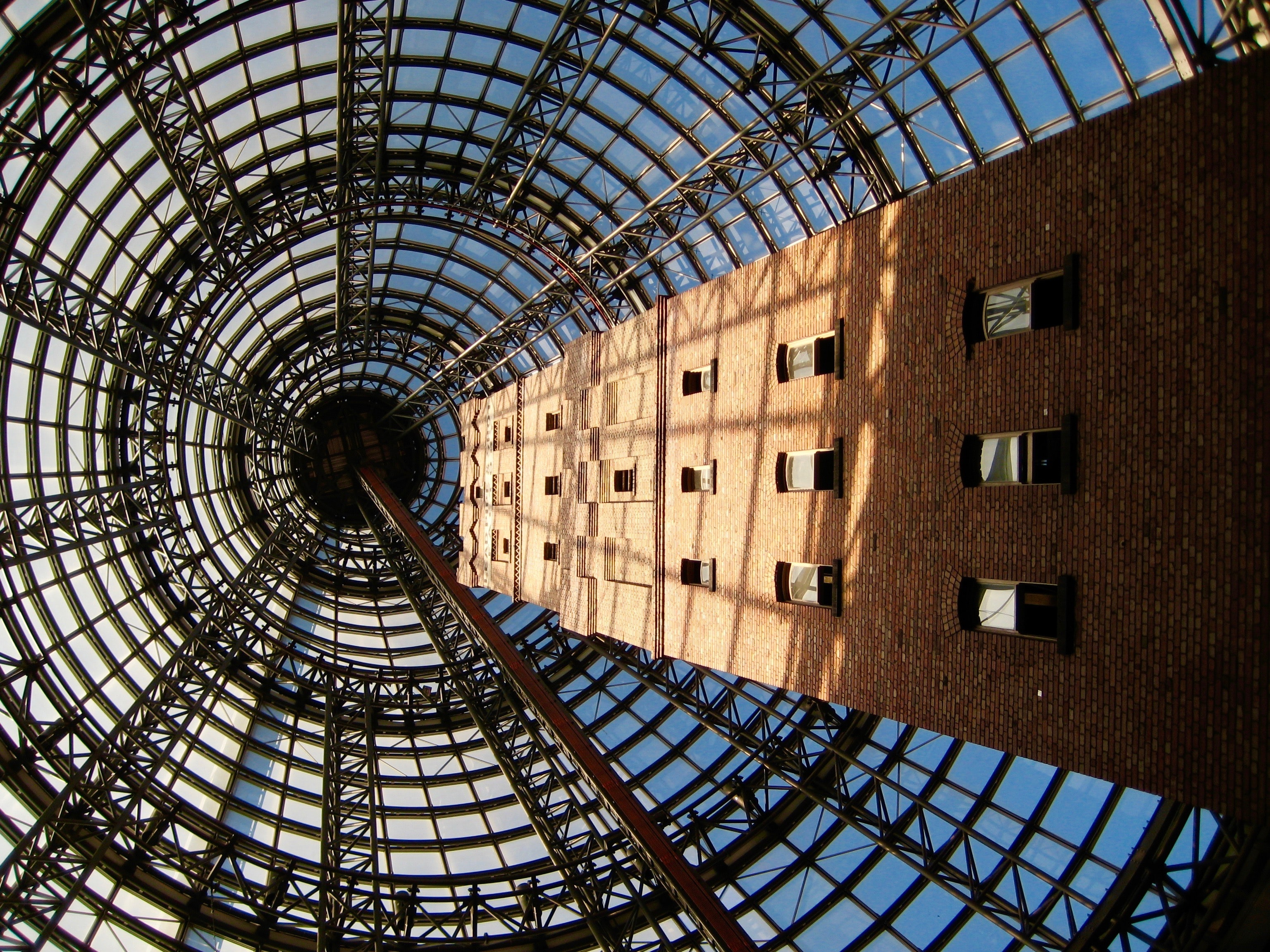 Upward perspective of a steel wire structure and building.