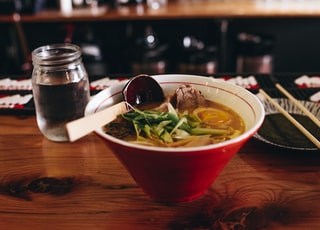 soup with vegetable beside chopsticks and glass of water