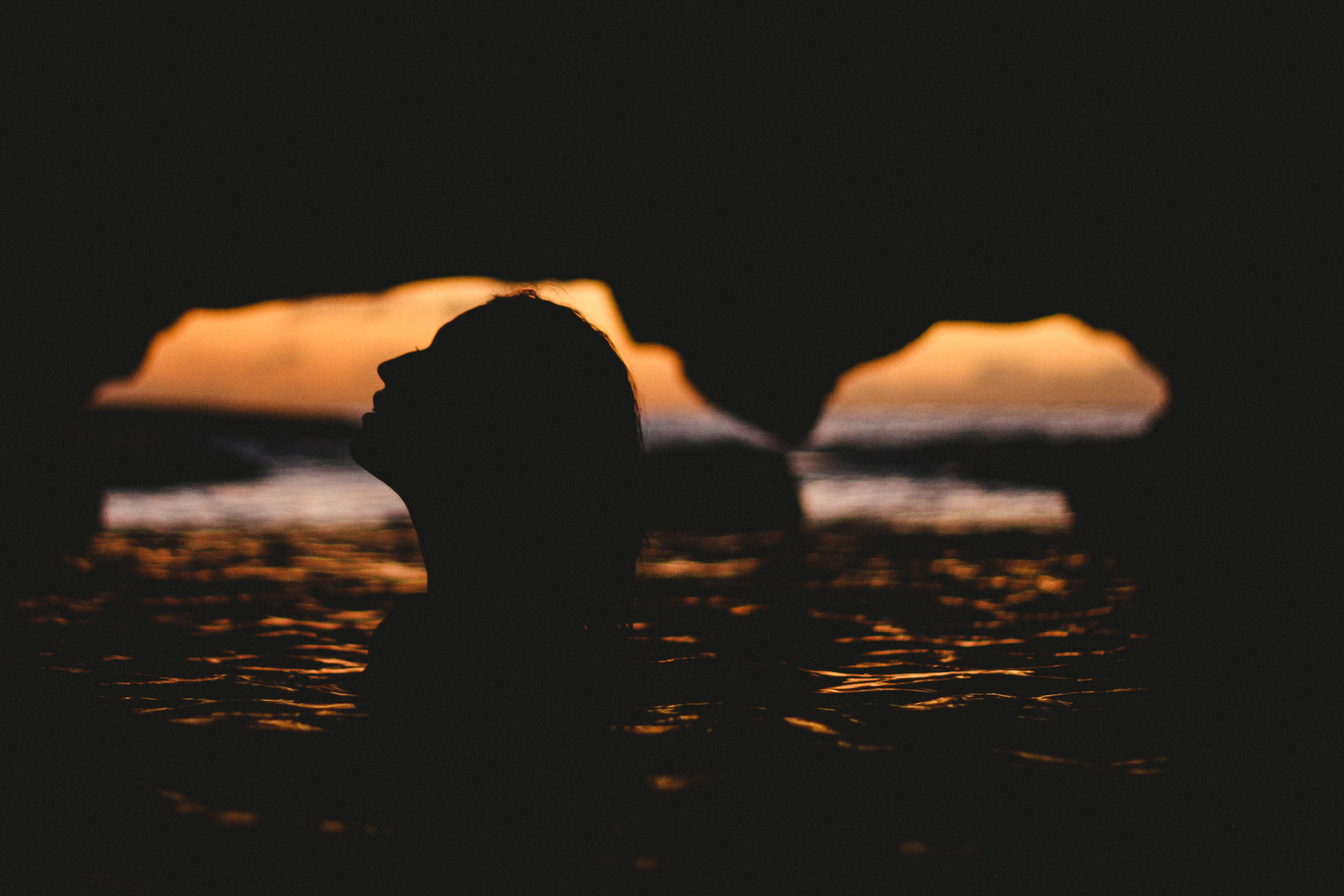 Silhouette of the profile of a woman in the water in a dark cave during sunset