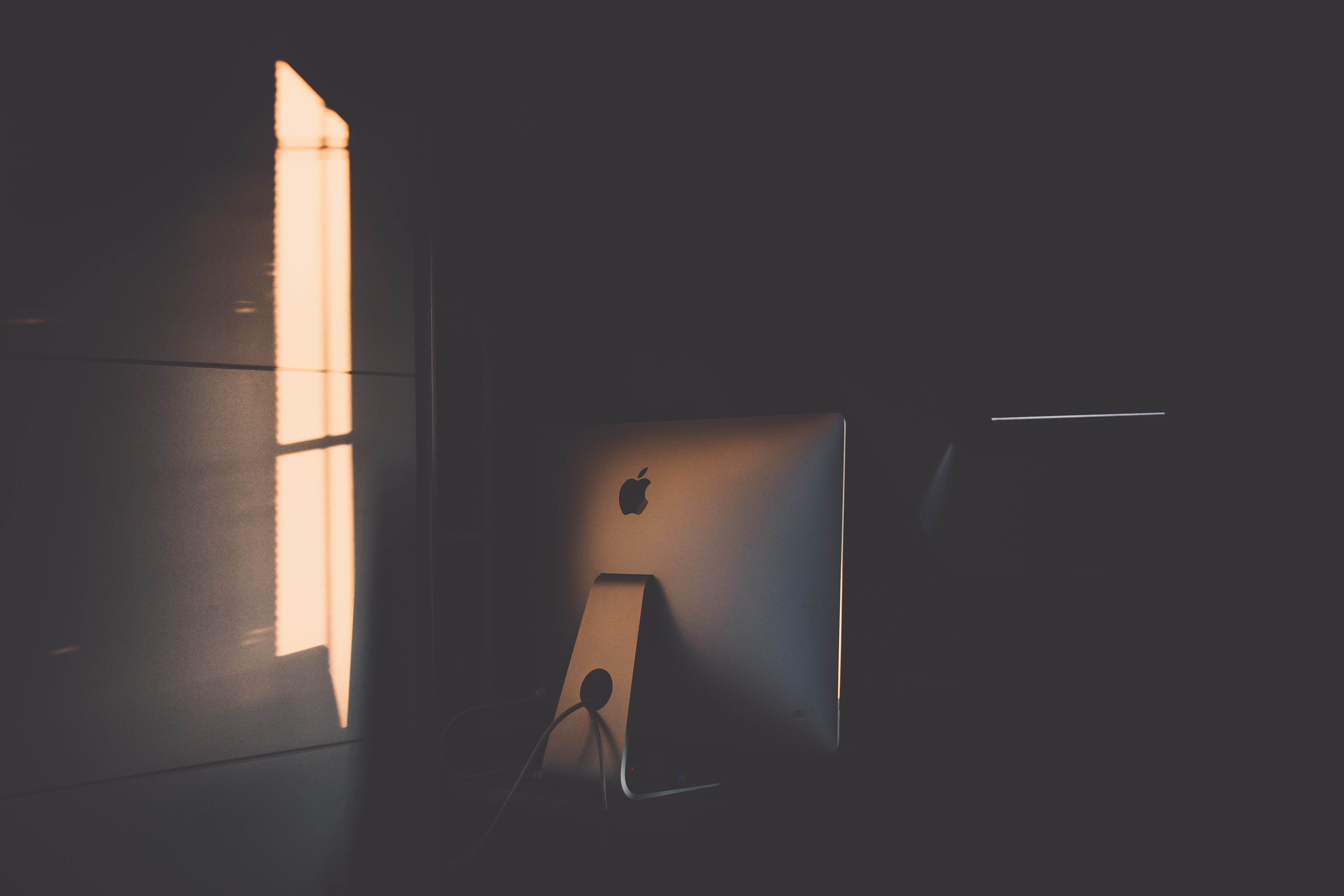 Room with shadow casting over an iMac computer on a desk in Sopron