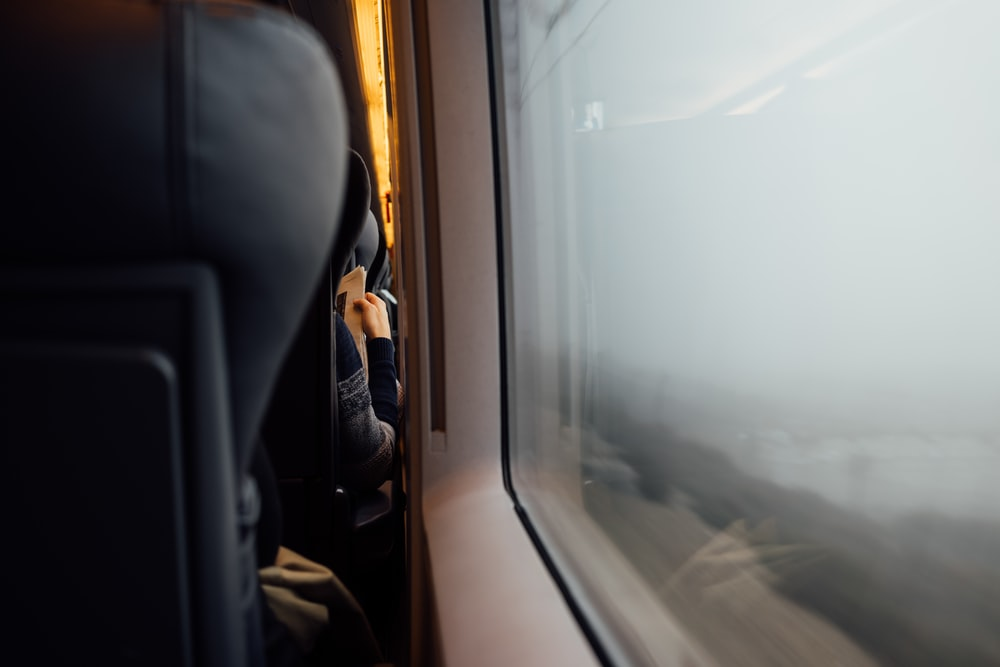 Person reading newspaper from behind with headrest in foreground near train carriage window