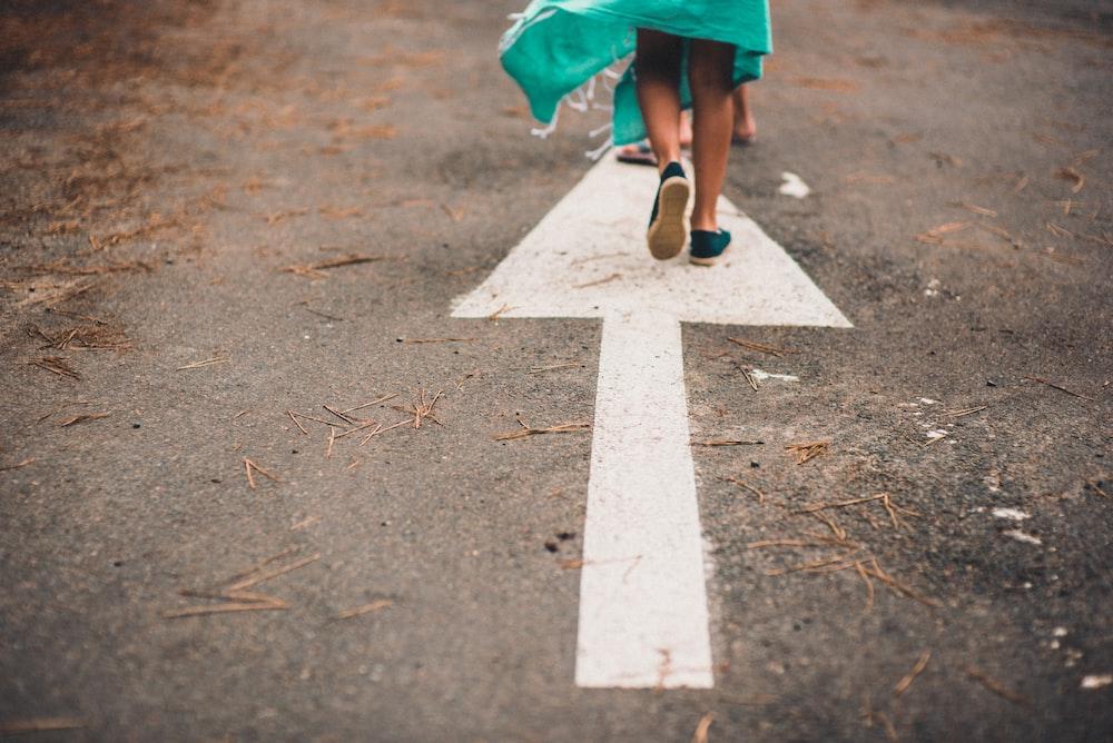 person walking on arrow street sign