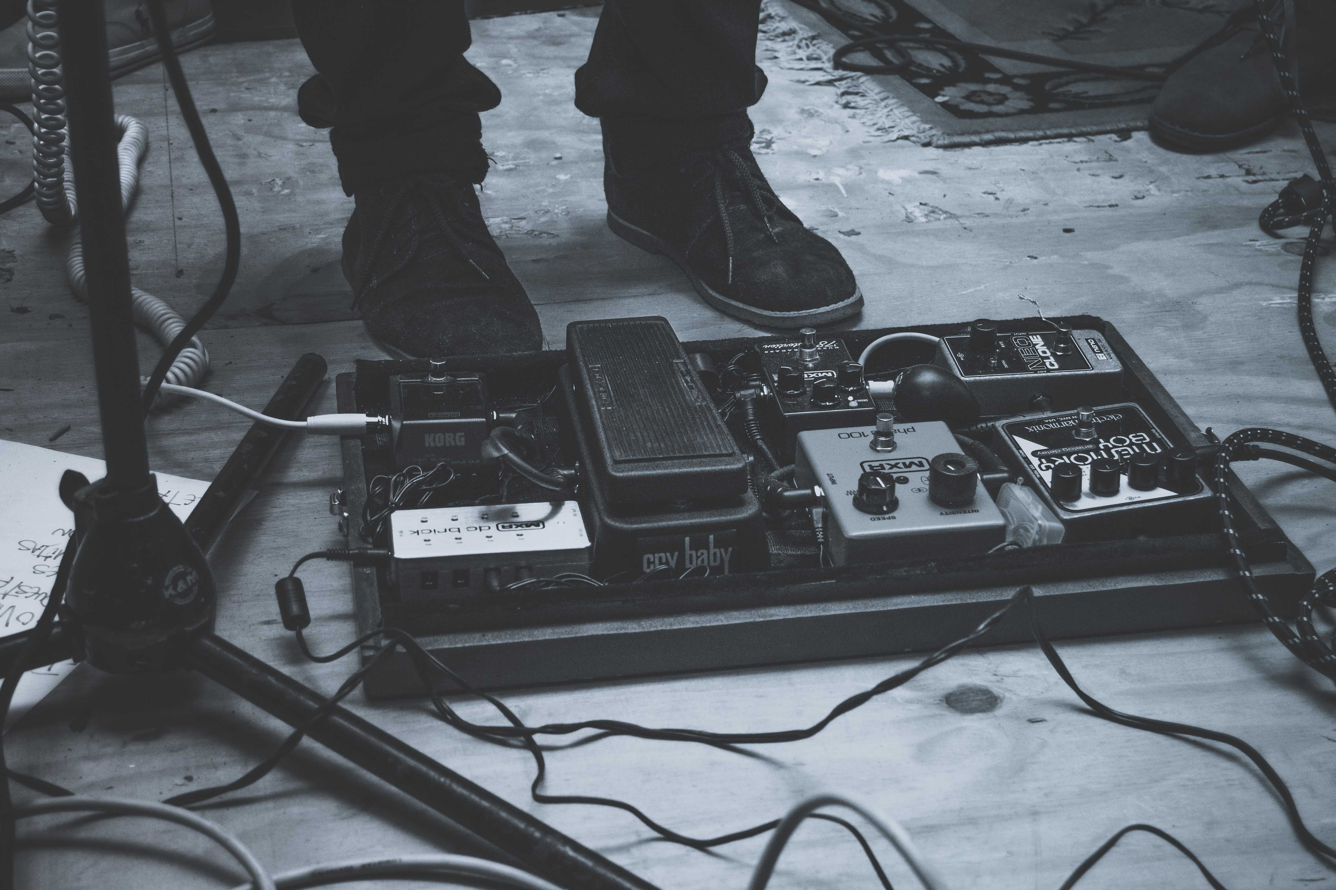 A low black-and-white shot of music equipment next to a person's shoes on stage