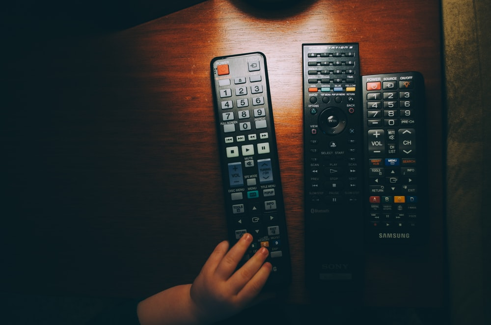 three black remote controls on wooden table