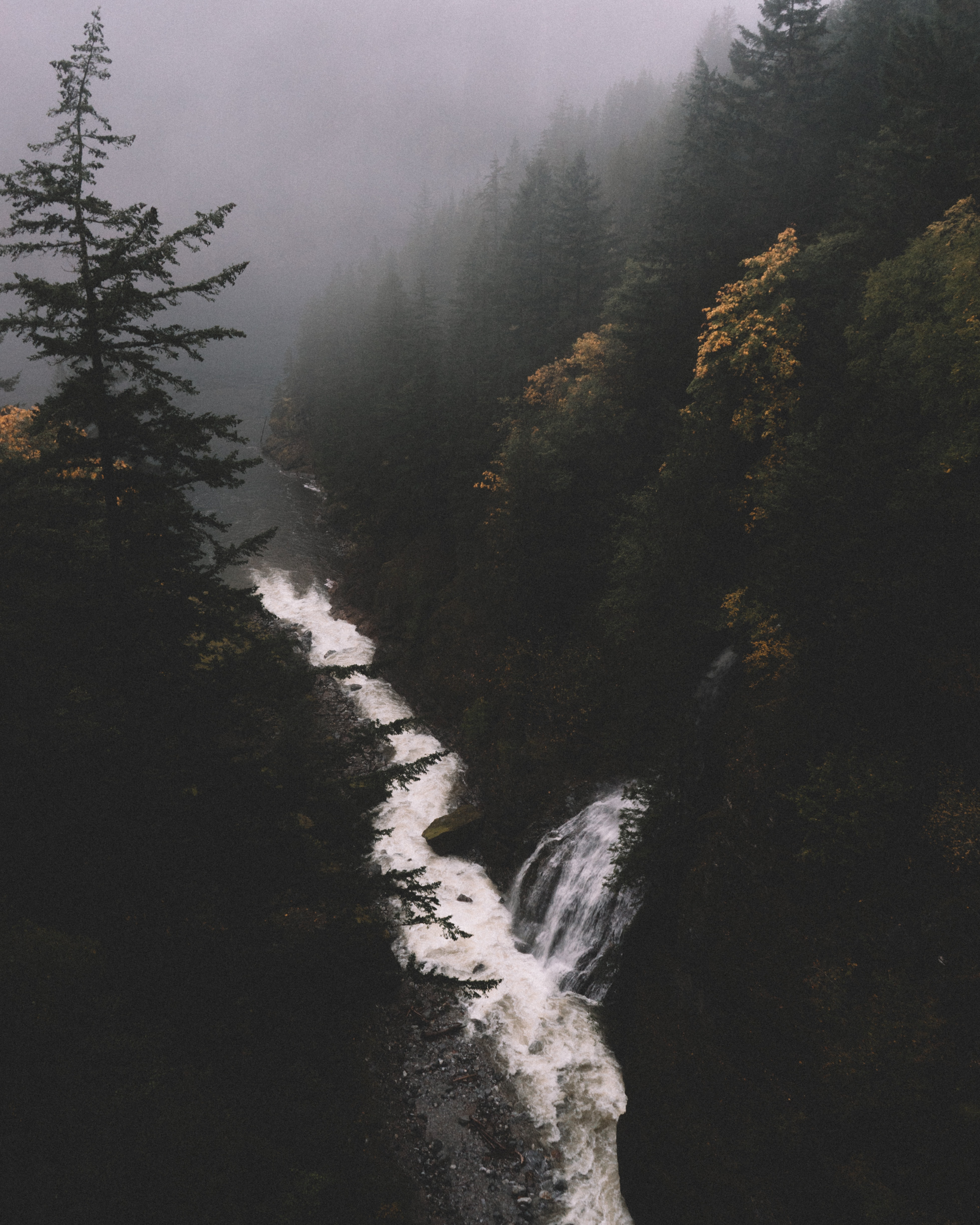 A drone shot of a waterfall tumbling down into a stream in a forest