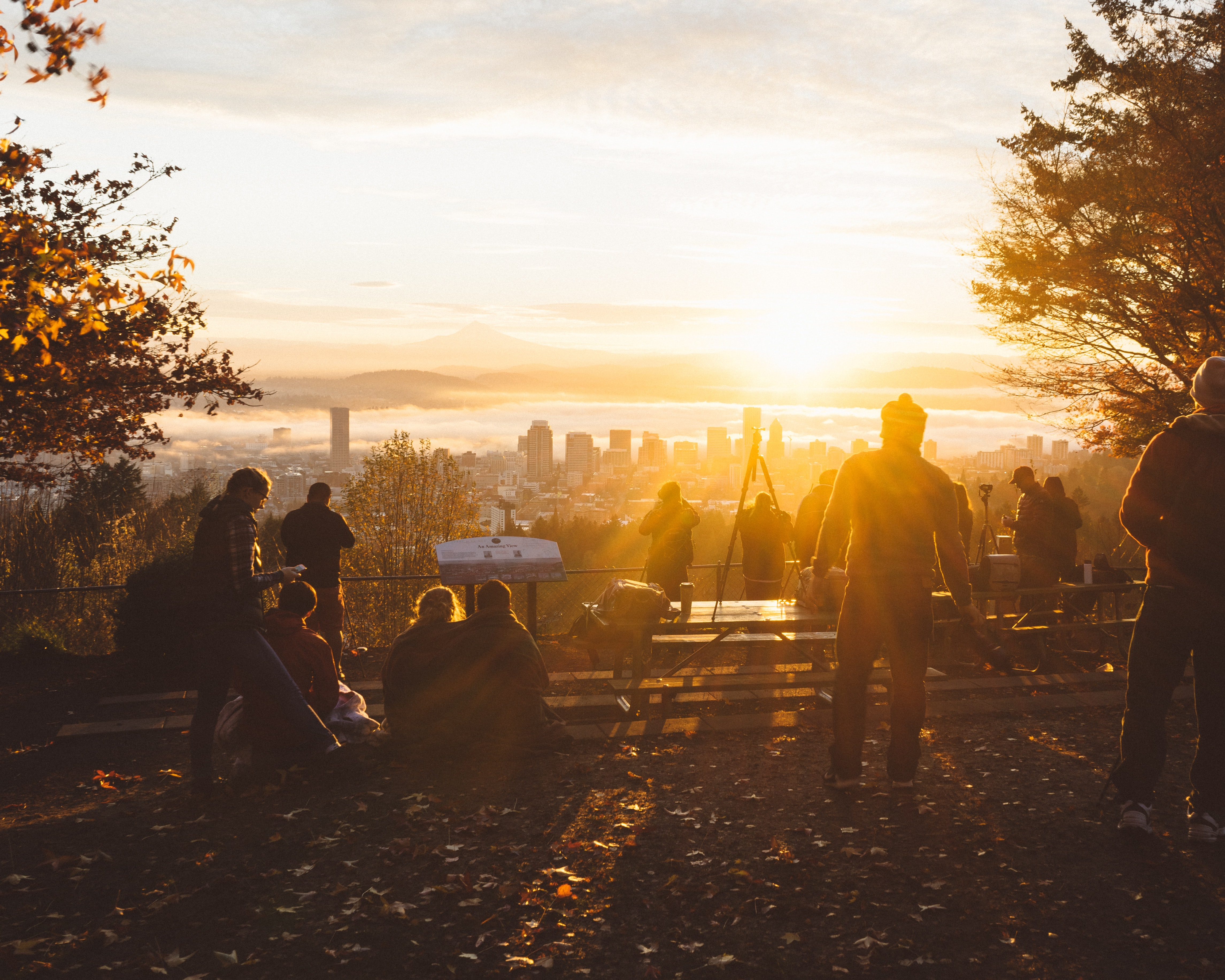A group of people watching the sunrise-or-sunset from a hilltop lookout spot at Pittock Mansion