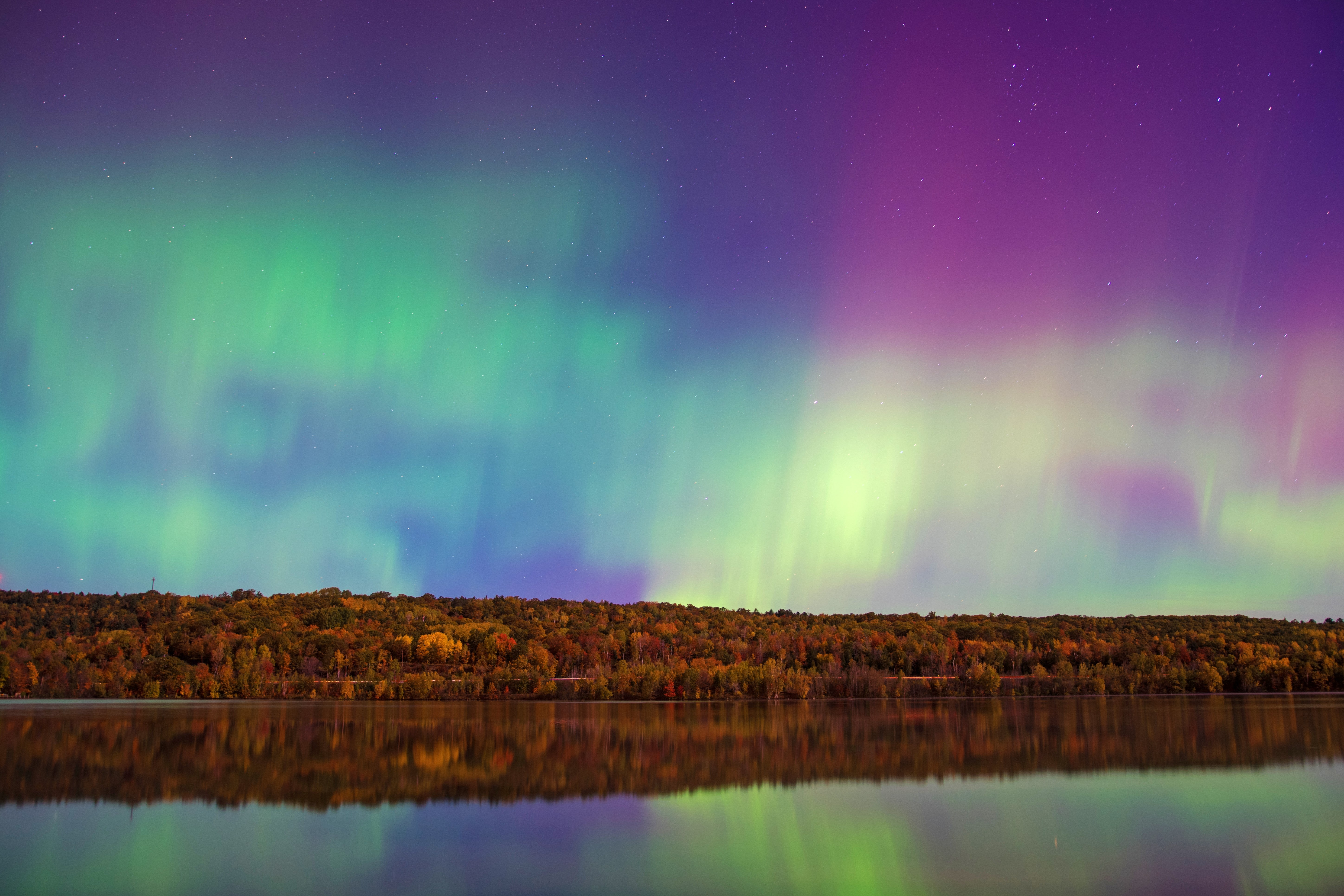 Colorful northern lights in the night sky over a tranquil lake in Houghton