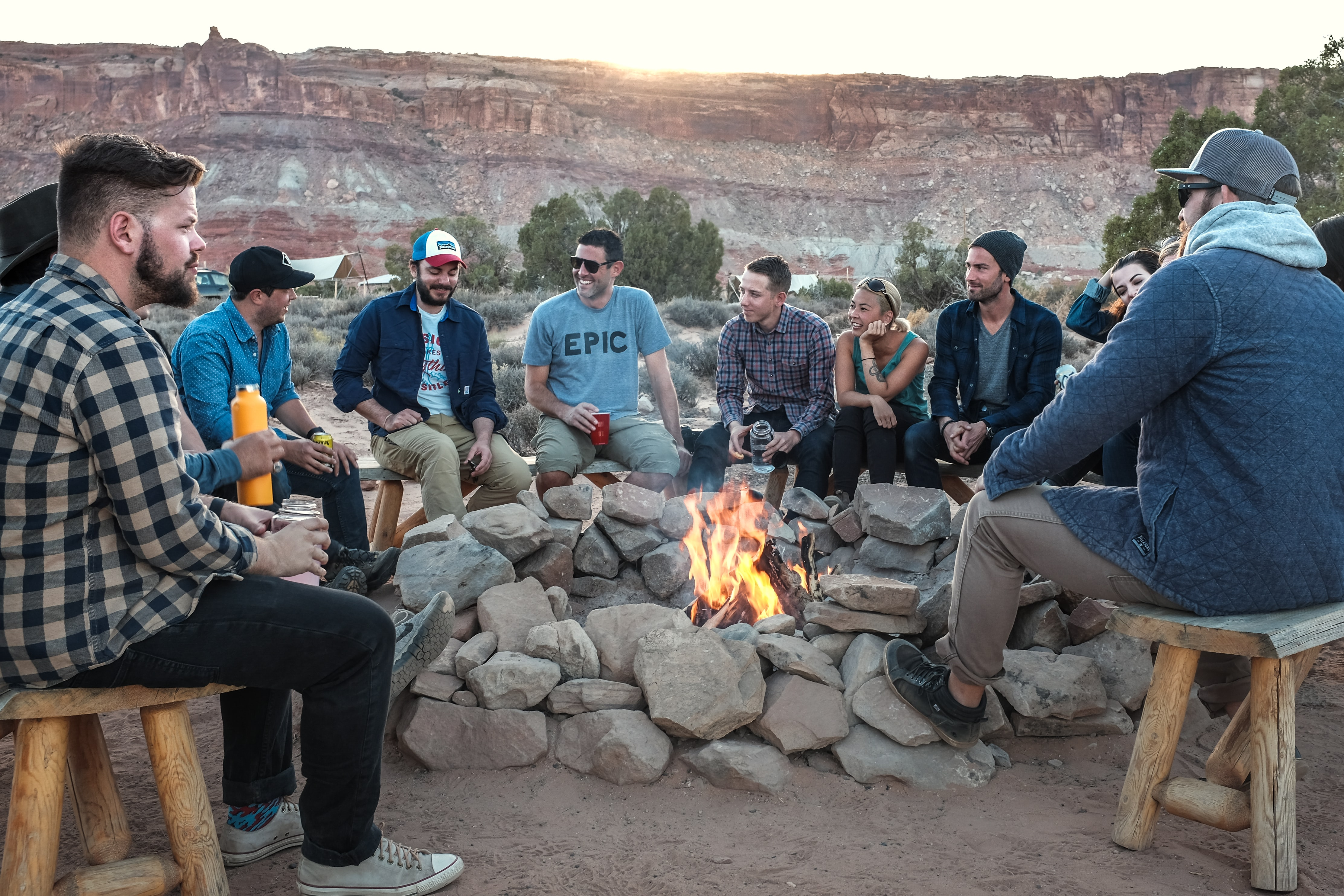 A group of smiling young people sitting around a fire pit in the mountains
